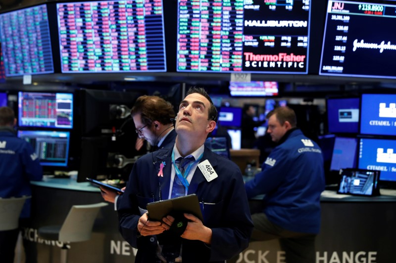 Traders work on the floor of the New York Stock Exchange (NYSE) as the building prepares to close indefinitely due to the coronavirus disease (COVID-19) outbreak in New York, U.S., March 20, 2020.  REUTERS/Lucas Jackson/Files