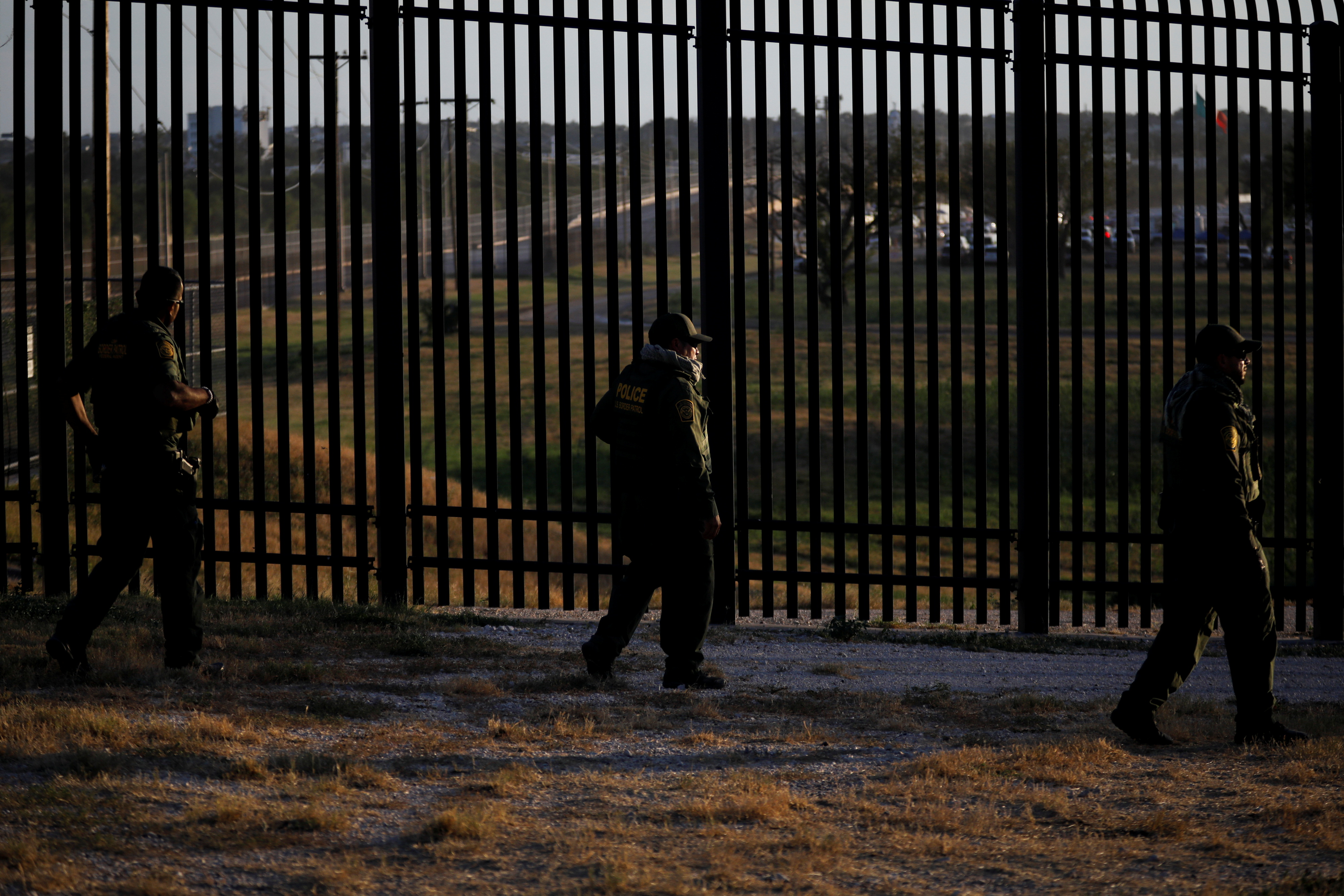 U.S. Border Patrol officers walk along the perimeter fence near the International Bridge between Mexico and the U.S., where migrants seeking asylum in the U.S. are waiting to be processed, in Del Rio, Texas, U.S., September 20, 2021. REUTERS/Marco Bello