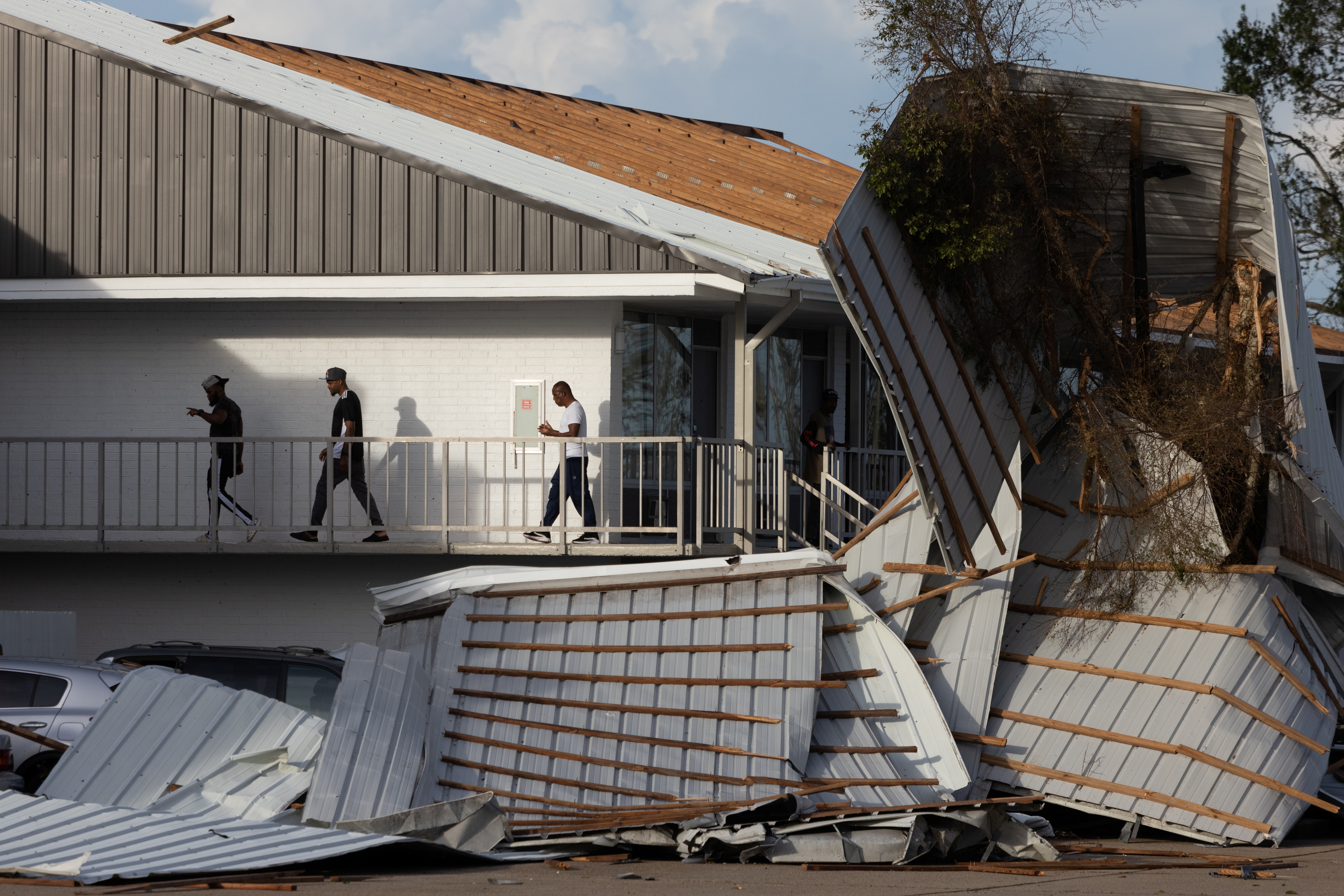 Men walk past the fallen scaffolding outside their hotel rooms in the aftermath of Hurricane Ida in Houma, Louisiana, U.S., August 30, 2021. REUTERS/Adrees Latif