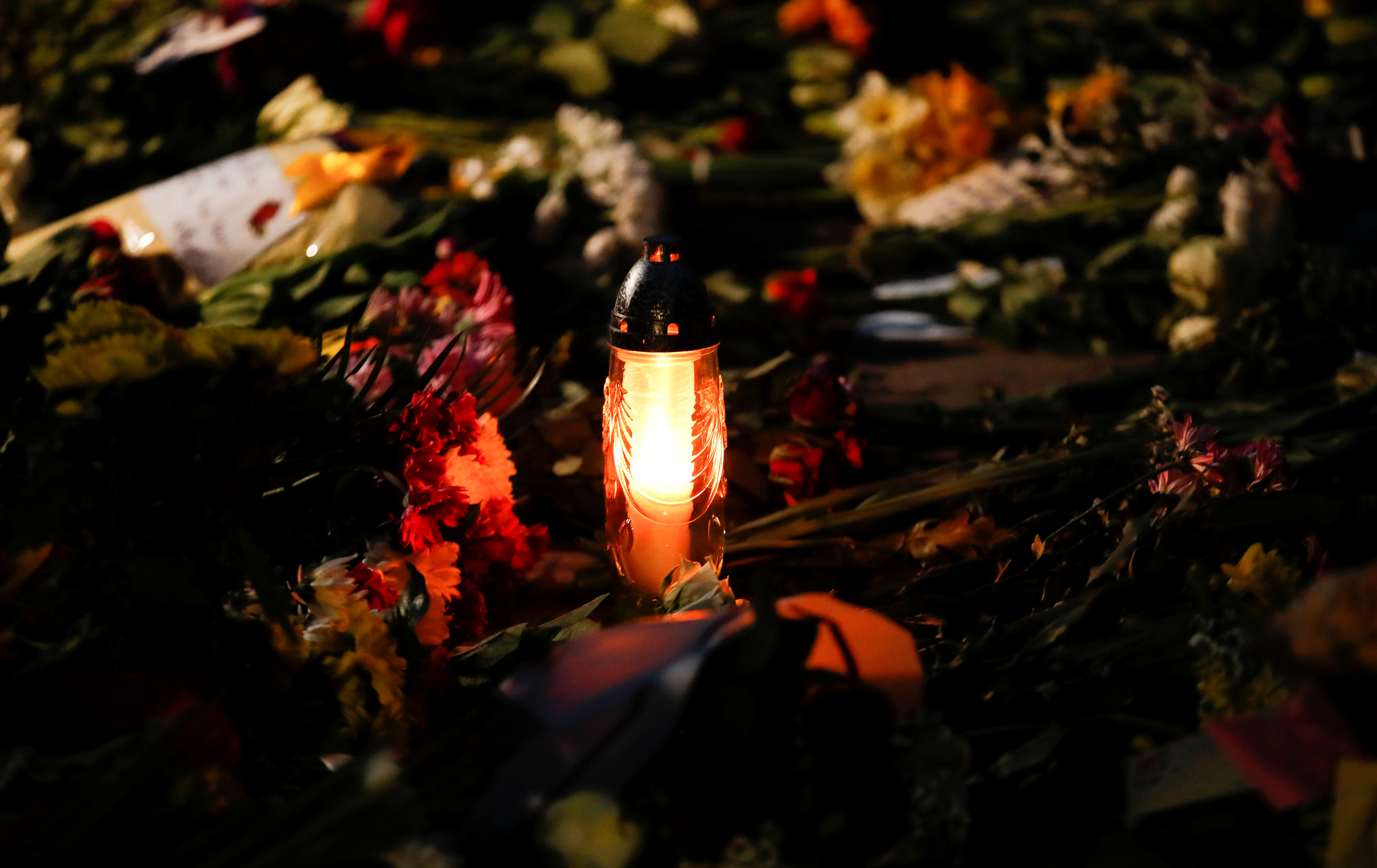 A candle is seen among flowers outside Windsor Castle after Britain's Prince Philip, husband of Queen Elizabeth, died at the age of 99, in Windsor, near London, Britain, April 9, 2021. REUTERS/Andrew Boyers