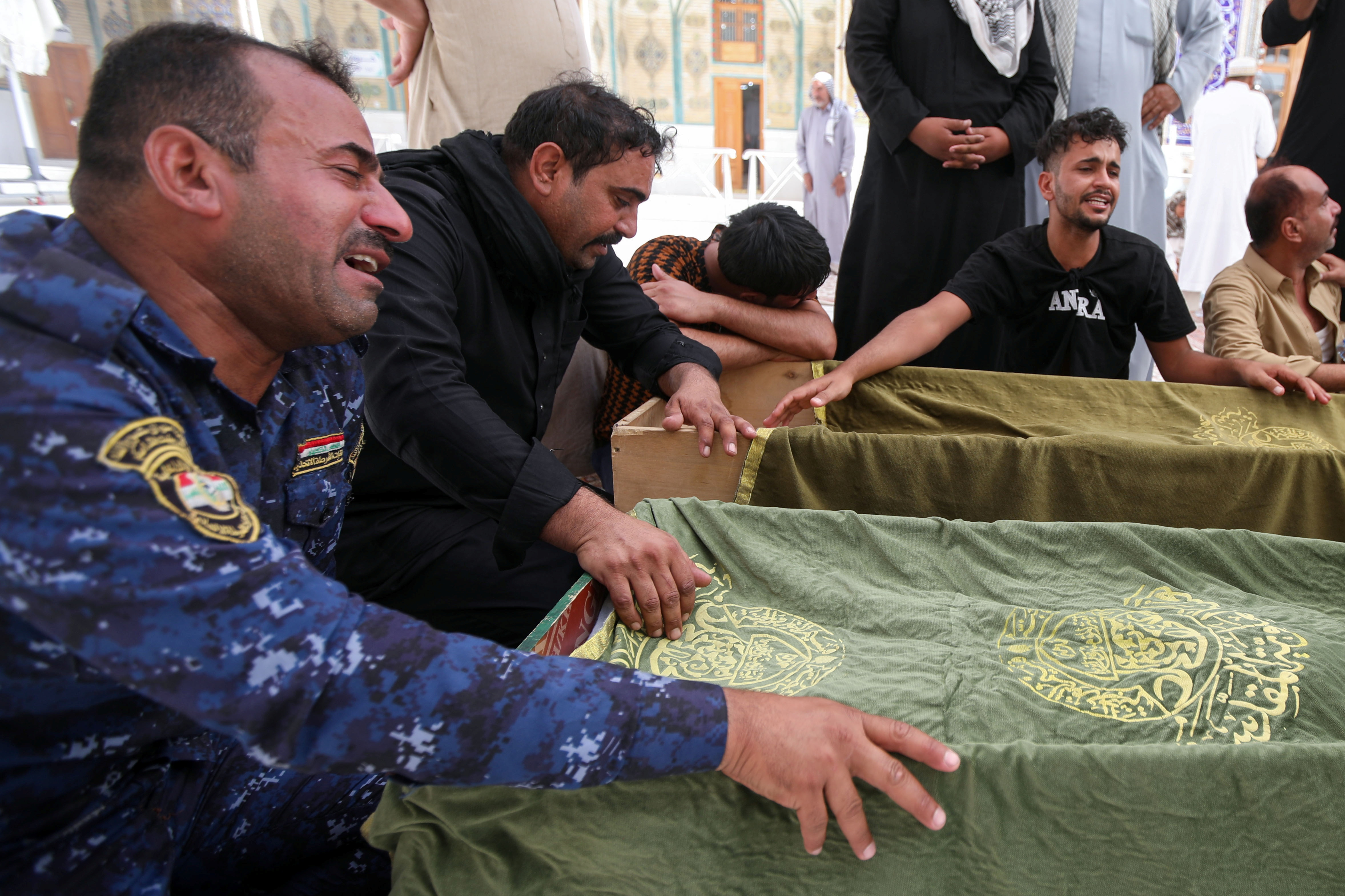 Mourners react next to the coffins of victims, who were killed in a fire that broke out at al-Hussain coronavirus hospital in Nassiriya, during a funeral in Najaf, Iraq, July 13, 2021. REUTERS/Alaa Al-Marjani