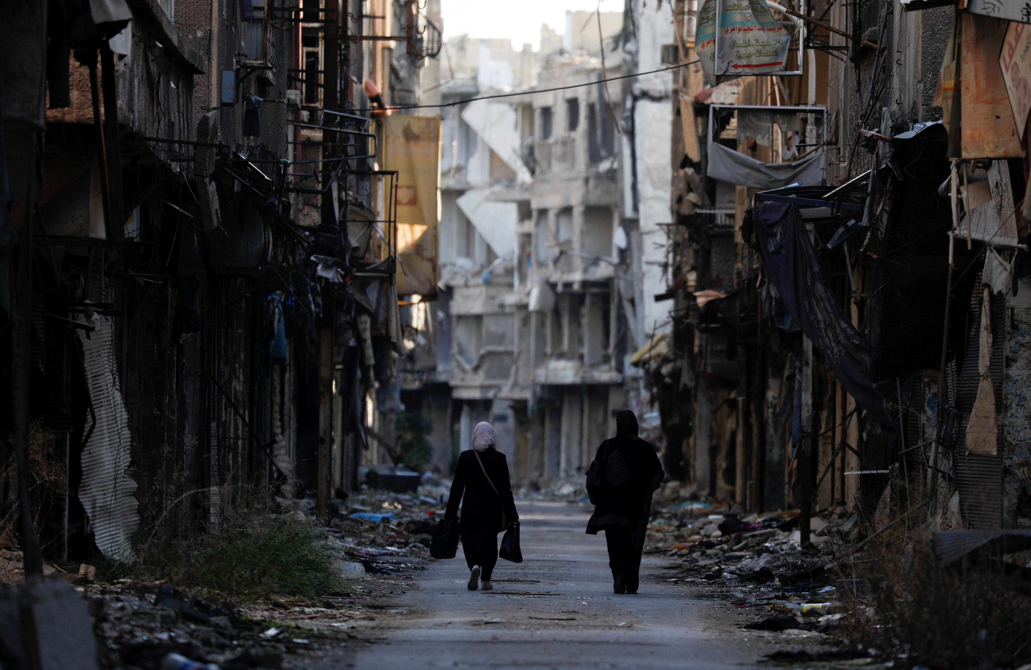 Women walk past damaged buildings at the Yarmouk Palestinian refugee camp on the southern outskirts of Damascus, Syria December 1, 2020.  REUTERS/Omar Sanadiki/File Photo