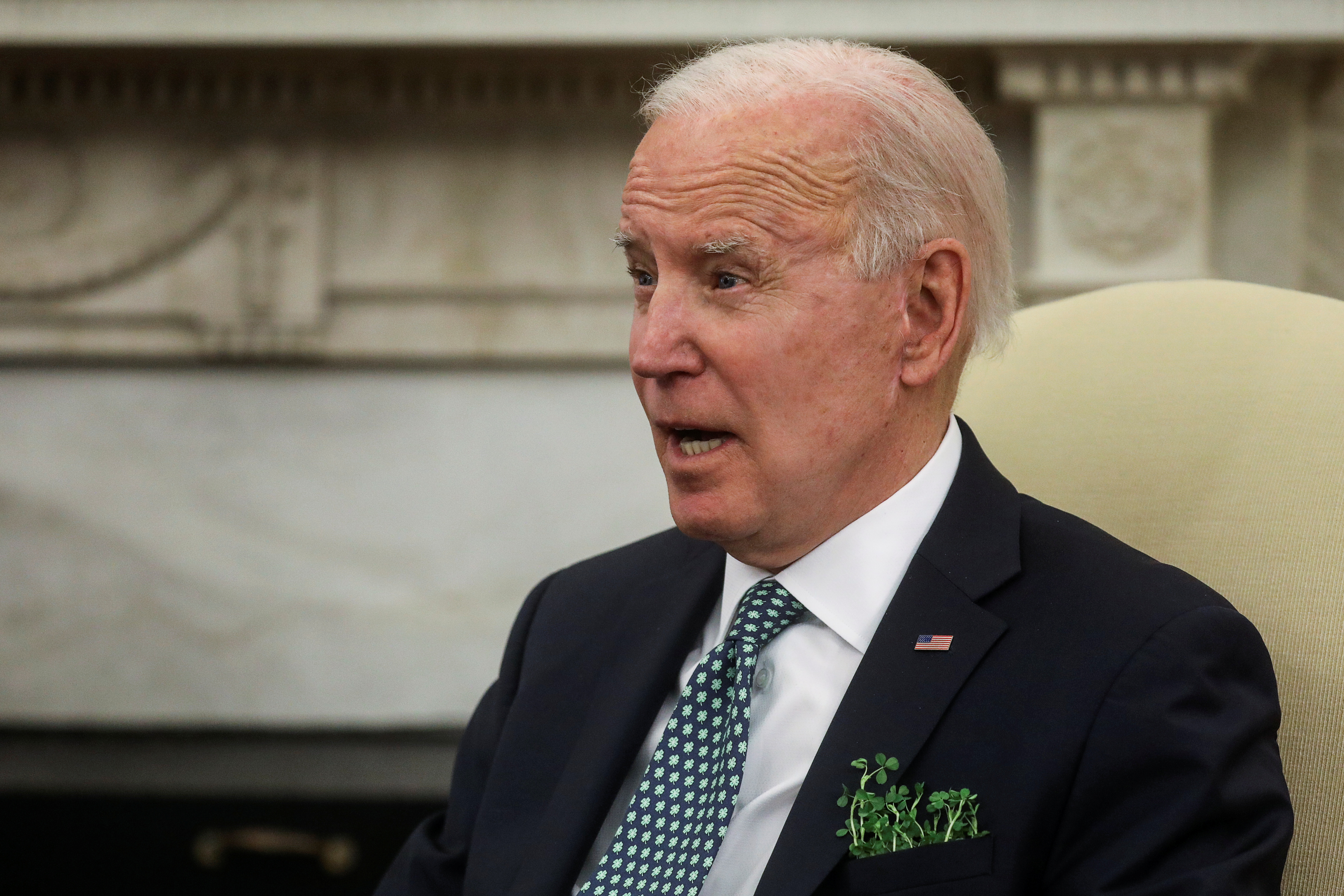 U.S. President Joe Biden wears a sprig of shamrock during a bilateral videoconference with Ireland's Prime Minister Micheal Martin  from the Oval Office at the White House in Washington, U.S., March 17, 2021. REUTERS/Leah Millis