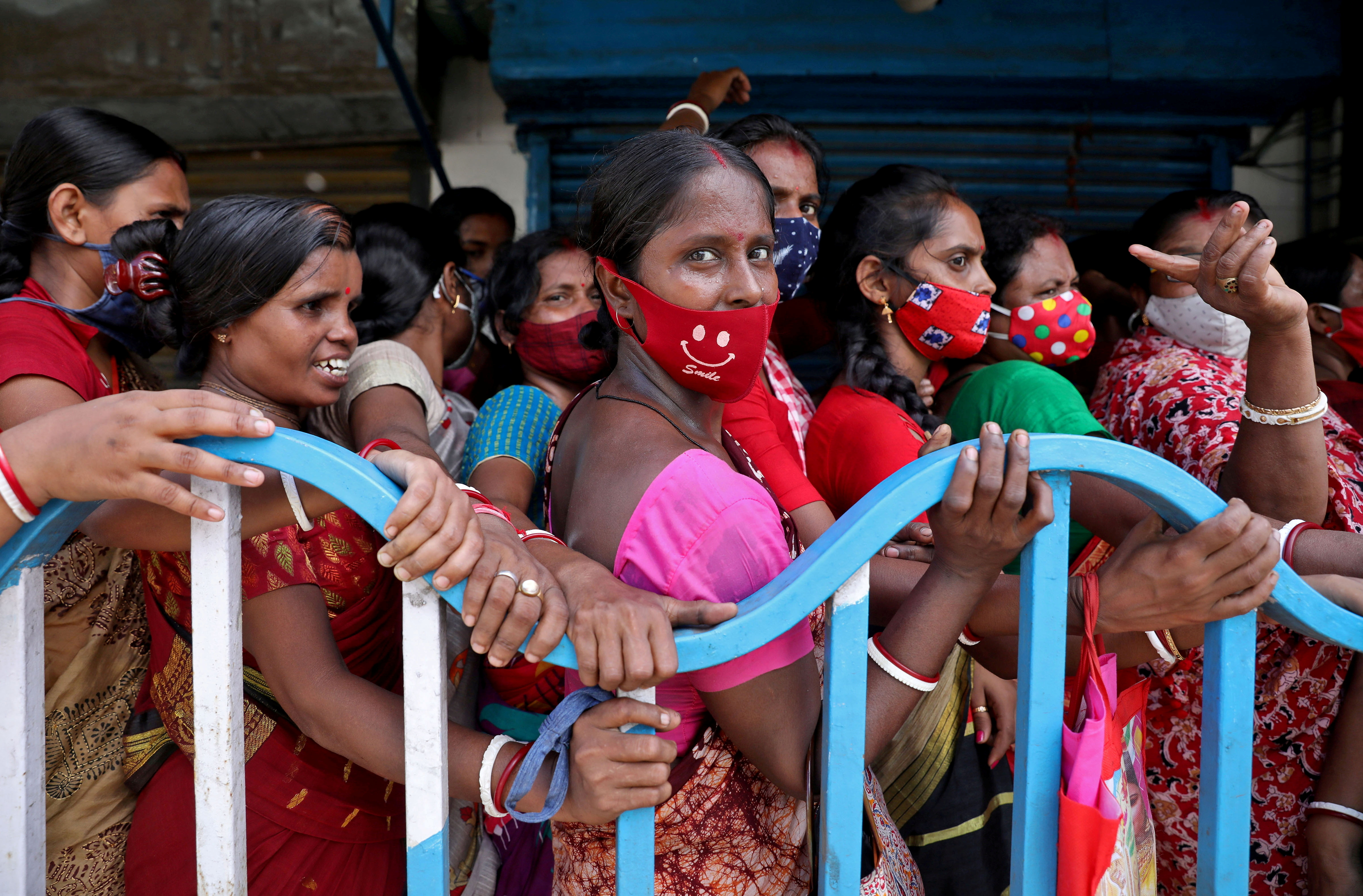 Women wait to receive a dose of COVISHIELD vaccine, a coronavirus disease (COVID-19) vaccine manufactured by Serum Institute of India, outside a vaccination centre in Kolkata, India, August 31, 2021. REUTERS/Rupak De Chowdhuri