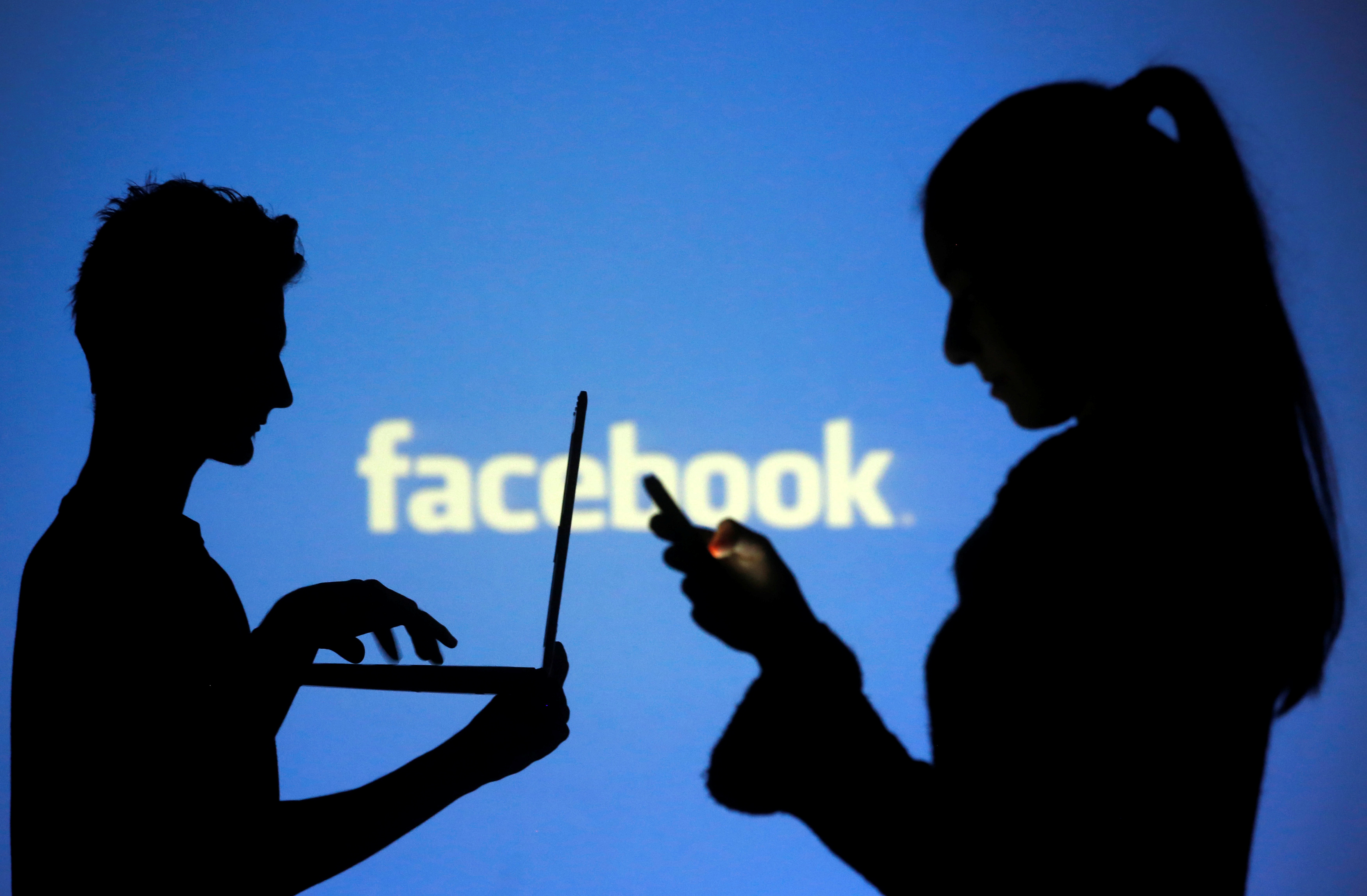 People are silhouetted as they pose with laptops in front of a screen projected with a Facebook logo, in this picture illustration taken in Zenica October 29, 2014. REUTERS/Dado Ruvic/File Photo