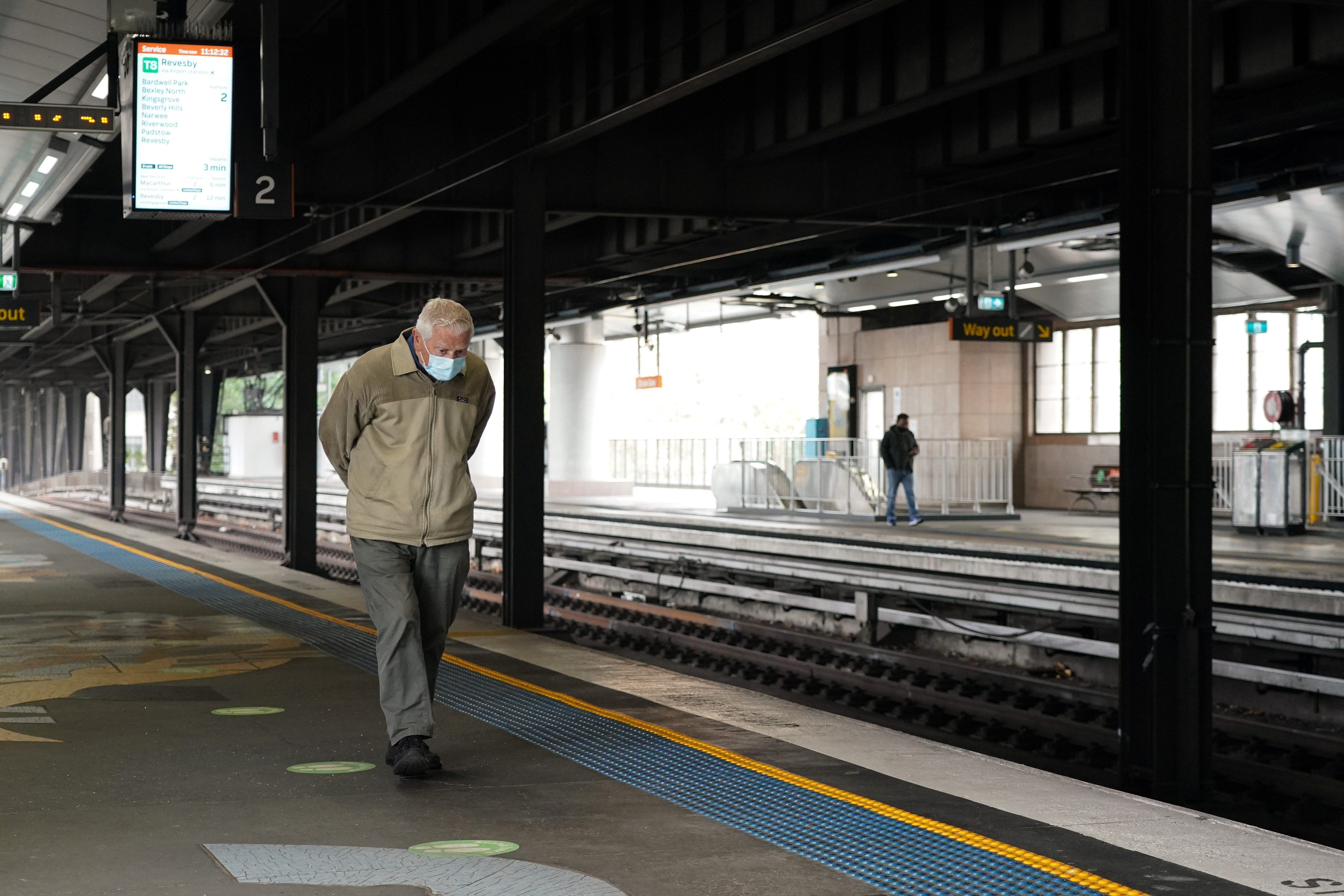 A lone passenger wearing a protective face mask walks along the deserted train platform at Circular Quay during a lockdown to curb the spread of a coronavirus disease (COVID-19) outbreak in Sydney, Australia, July 1, 2021. REUTERS/Loren Elliott
