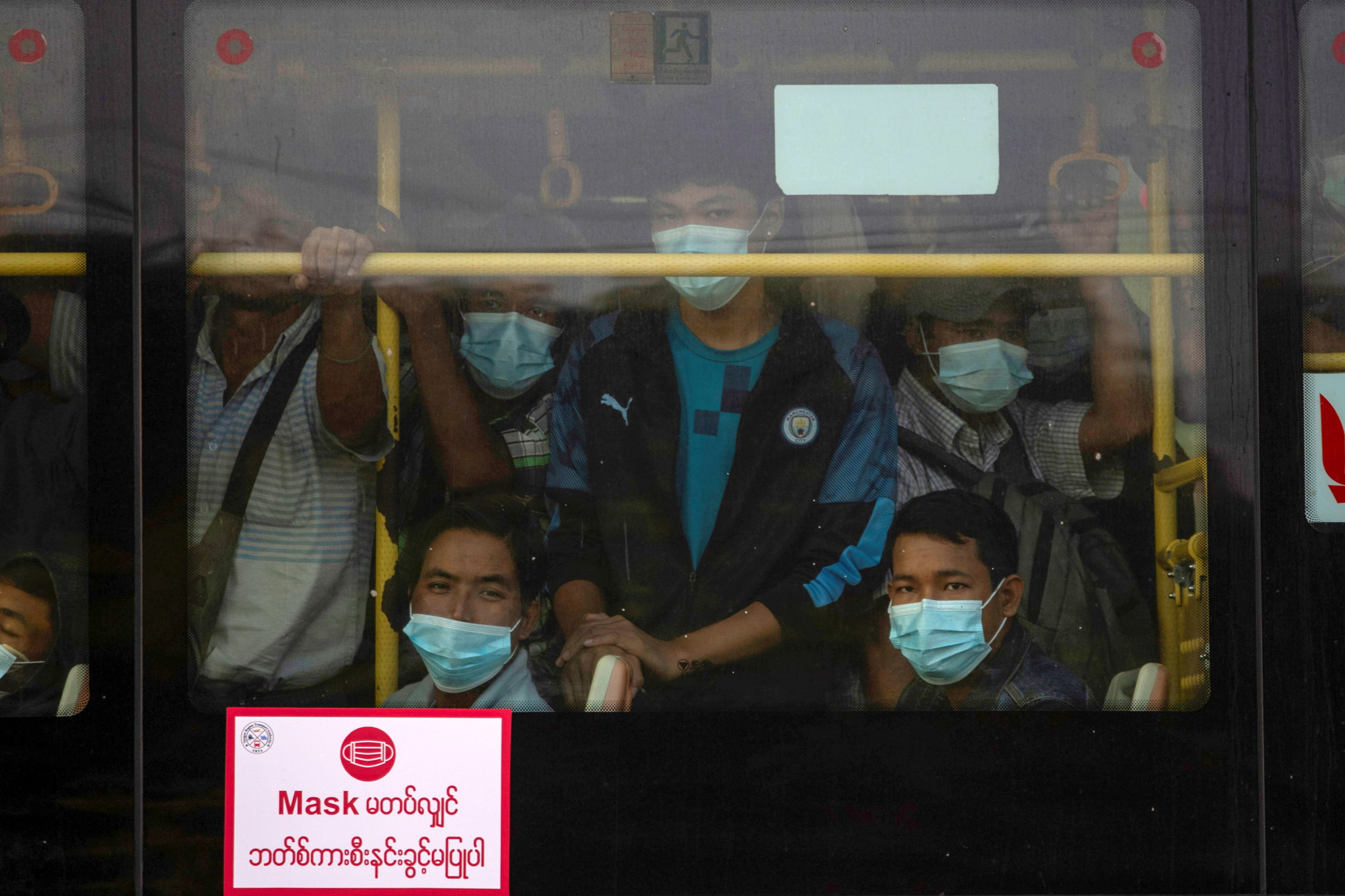 Commuters wearing protective masks ride a bus, amid the outbreak of the coronavirus disease (COVID-19), in Yangon, Myanmar, December 7, 2020. REUTERS/Shwe Paw Mya Tin