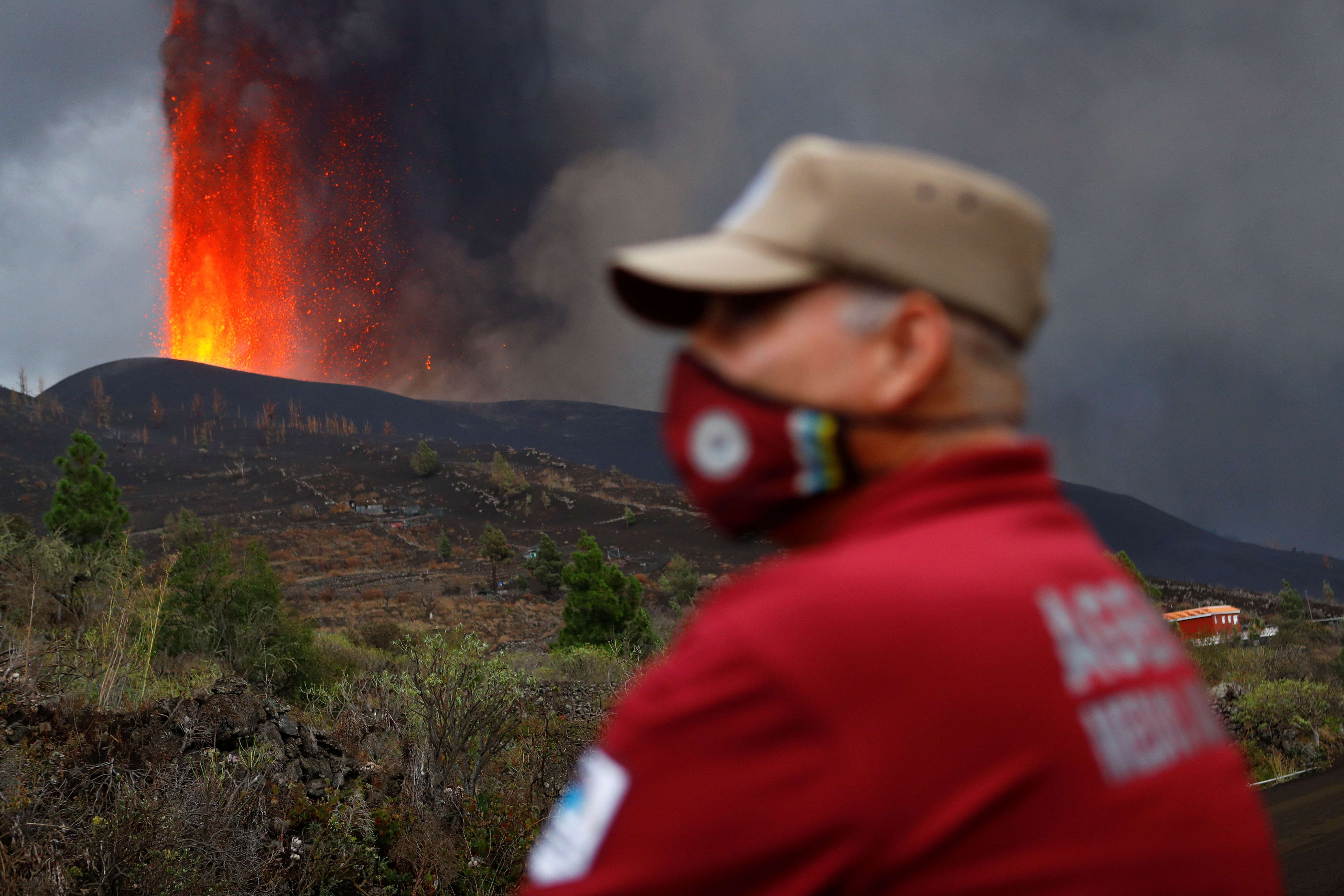An environmental agent looks on as lava rises following the eruption of a volcano on the Island of La Palma, in Tacande, Spain September 22, 2021. REUTERS/Borja Suarez