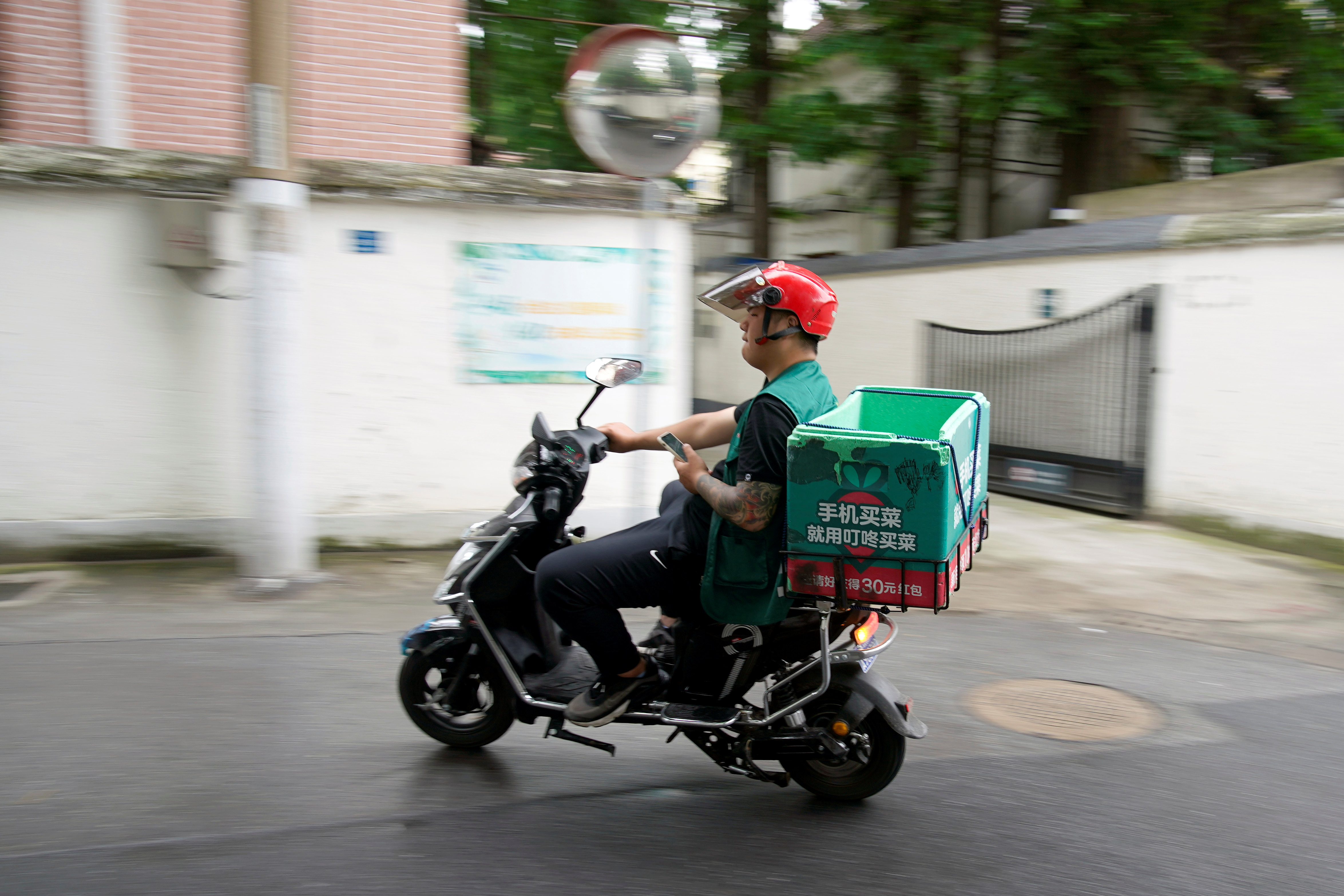 A delivery worker of Chinese online grocery Dingdong Maicai is seen on a street in Shanghai, China June 10, 2021. REUTERS/Aly Song