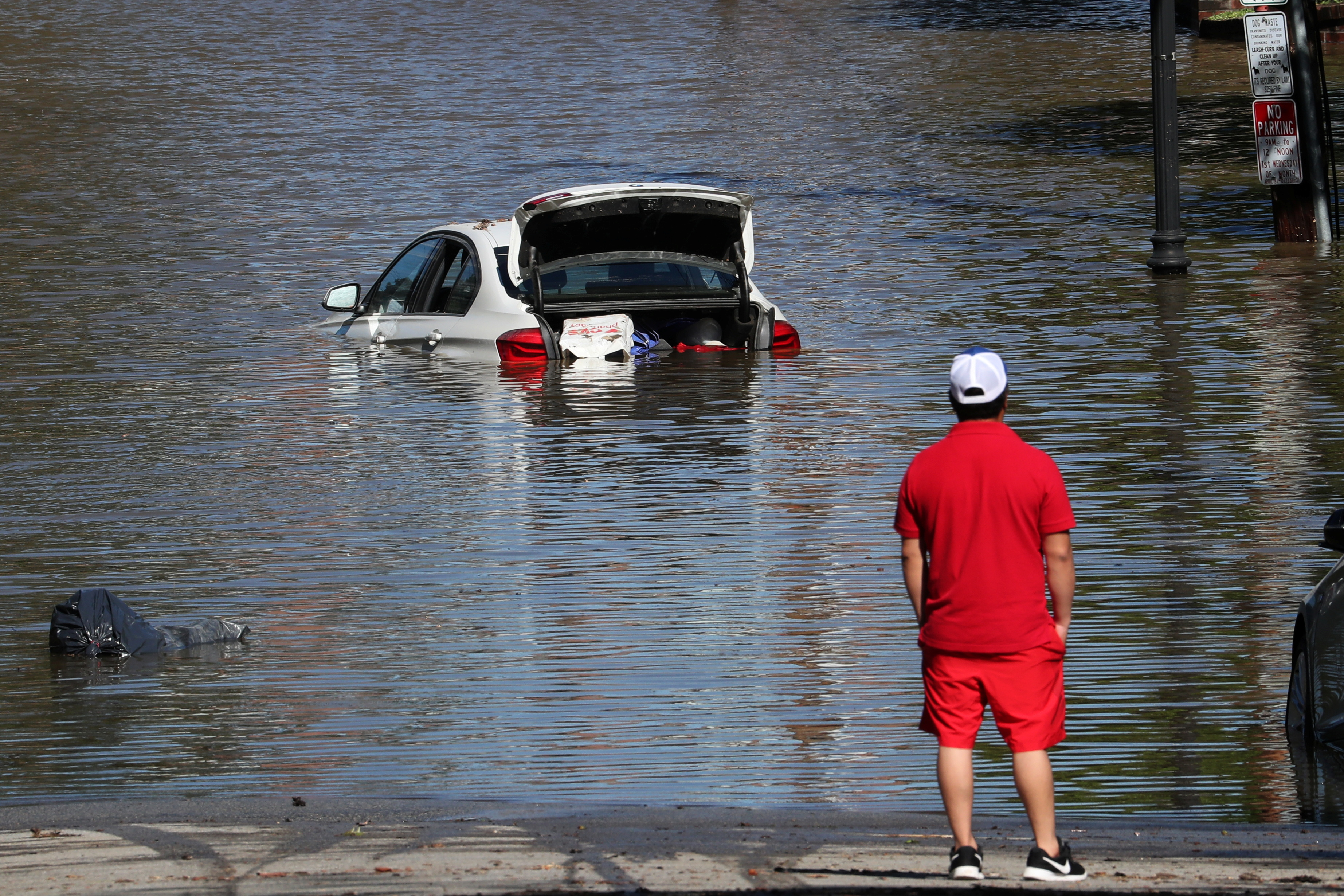 A man looks at a car in floodwaters after remnants of Ida brought drenching rain, flash floods and tornadoes to parts of the Northeast in Mamaroneck, New York, September 2, 2021. REUTERS/Mike Segar