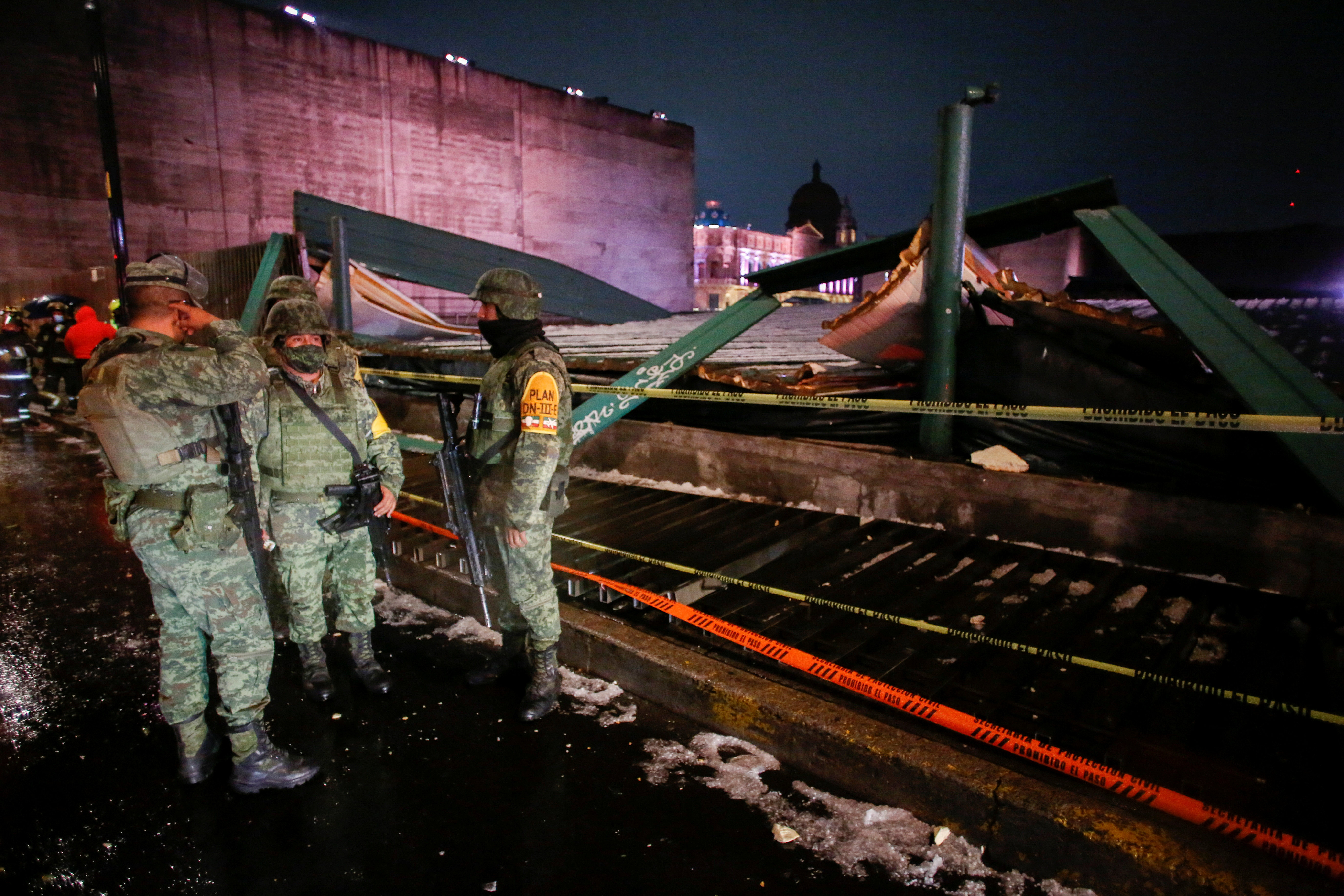 Soldiers chat at a scene where the roof protecting the