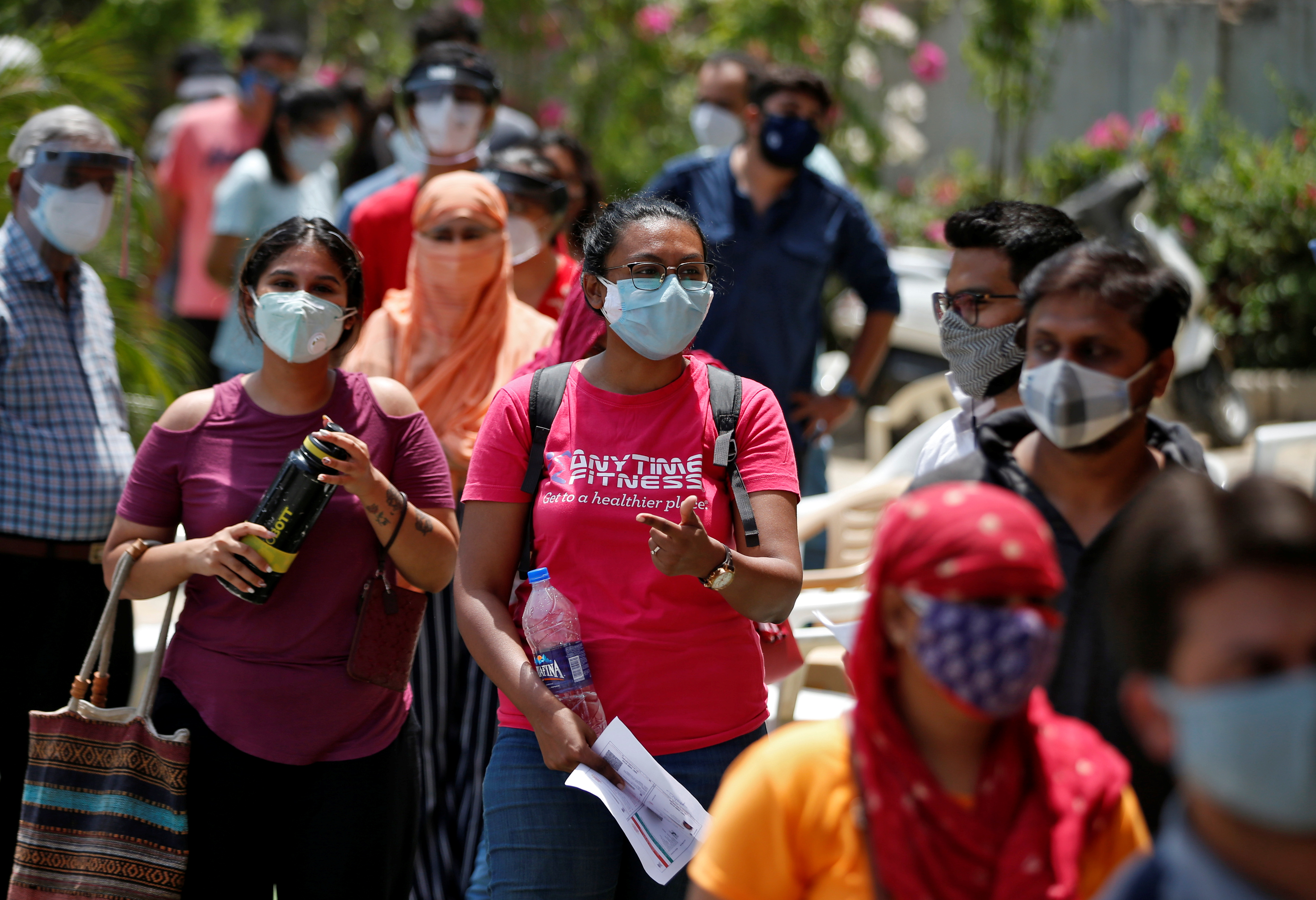 People wearing protective face masks wait to receive a dose of COVISHIELD, a coronavirus disease (COVID-19) vaccine manufactured by Serum Institute of India, outside a vaccination centre in Ahmedabad, India, May 1, 2021. REUTERS/Amit Dave
