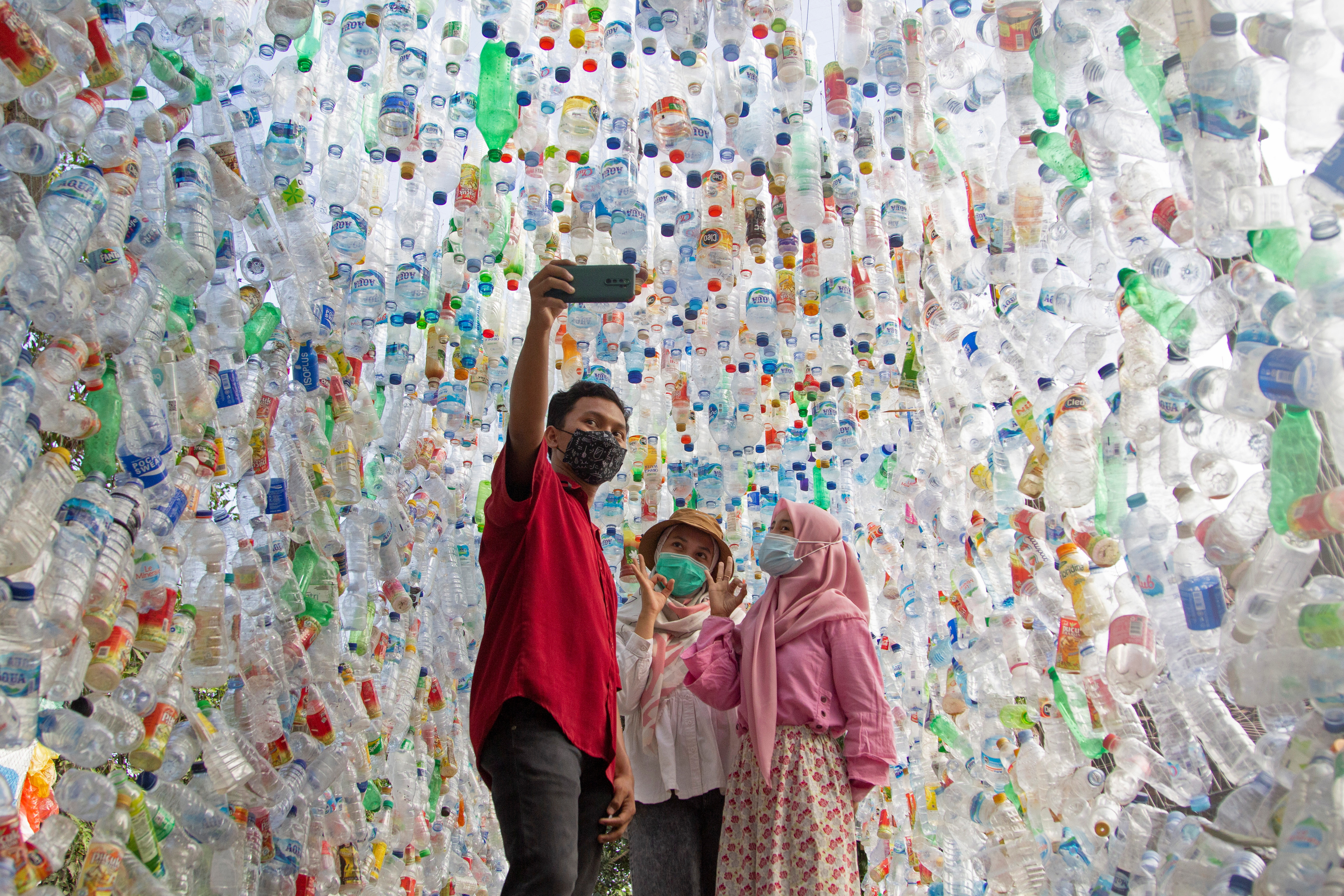 """People take selfie pictures at """"Terowongan 4444"""" or 4444 tunnel, built from plastic bottles collected from several rivers around the city in three years, at the plastic museum constructed by Indonesia's environmental activist group Ecological Observation and Wetlands Conservation (ECOTON) in Gresik regency near Surabaya, East Java province, Indonesia, September 28, 2021. Picture taken September 28, 2021. REUTERS/Prasto Wardoyo"""