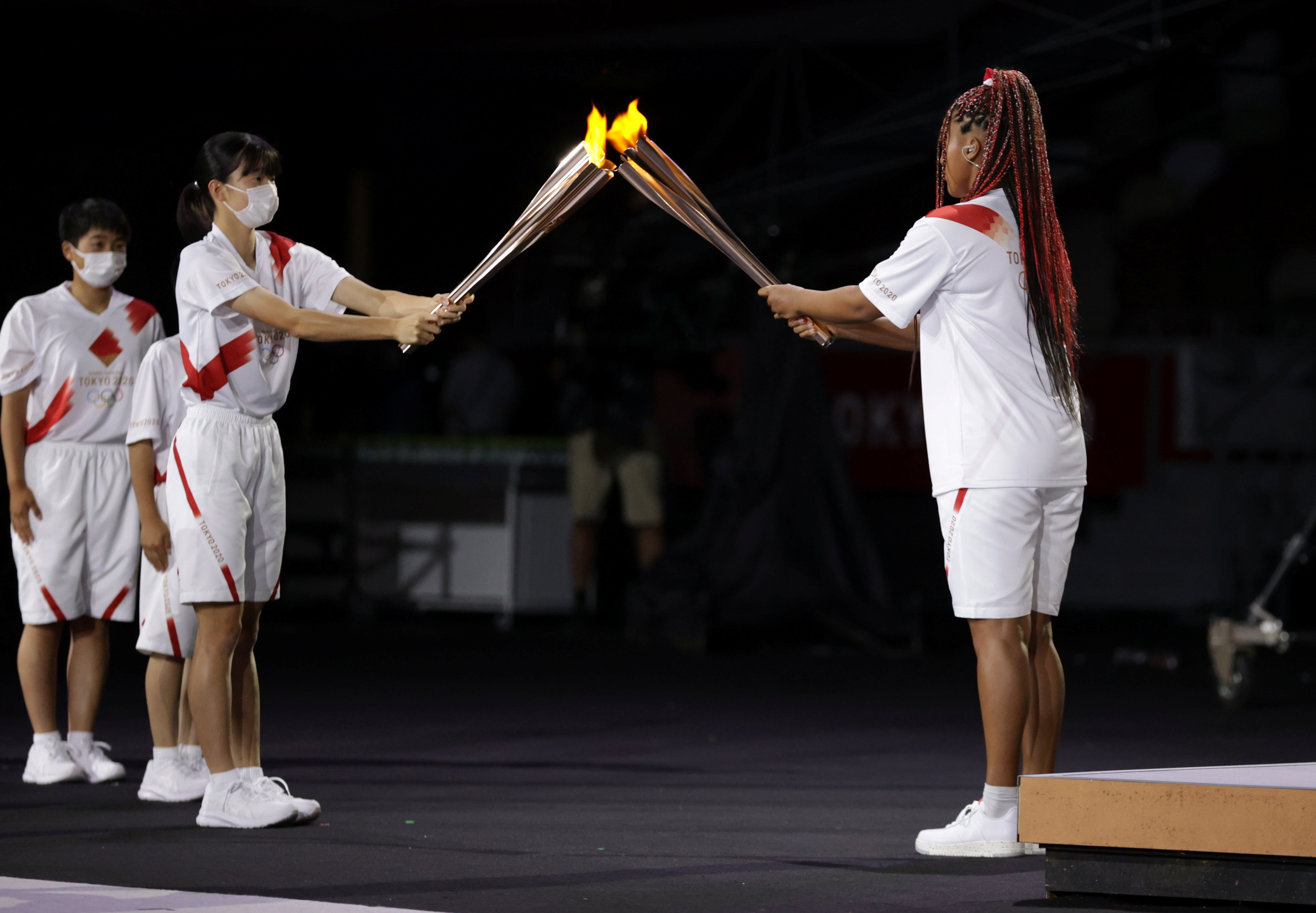 Tokyo 2020 Olympics - The Tokyo 2020 Olympics Opening Ceremony - Olympic Stadium, Tokyo, Japan - July 23, 2021. The Olympic flame is transferred to a torch carried by Naomi Osaka of Japan REUTERS/Hannah Mckay