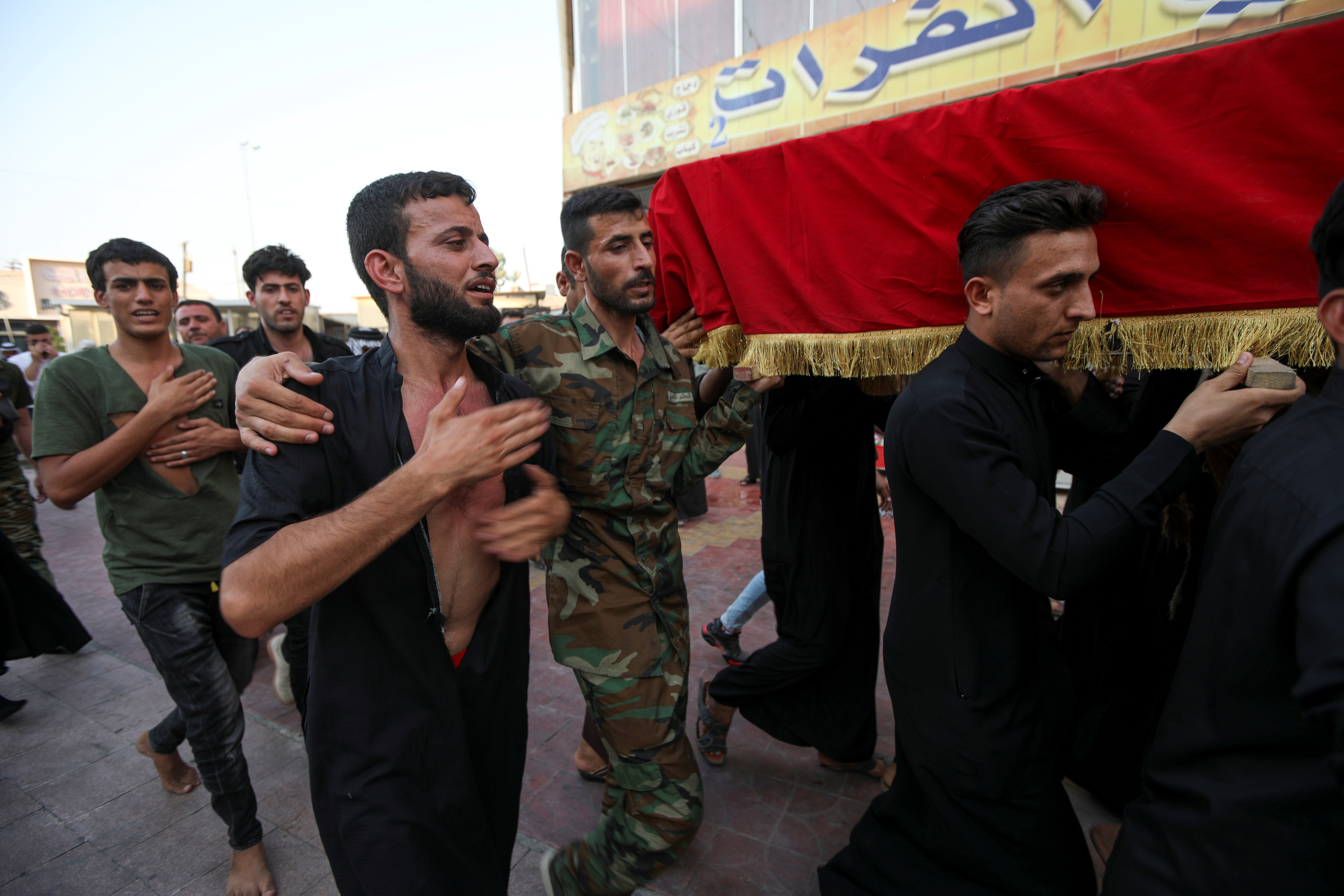 Mourners carry the coffin of a policeman, who was killed in an attack in Kirkuk, during a funeral in Najaf, Iraq, September 5, 2021. REUTERS/Alaa Al-Marjani