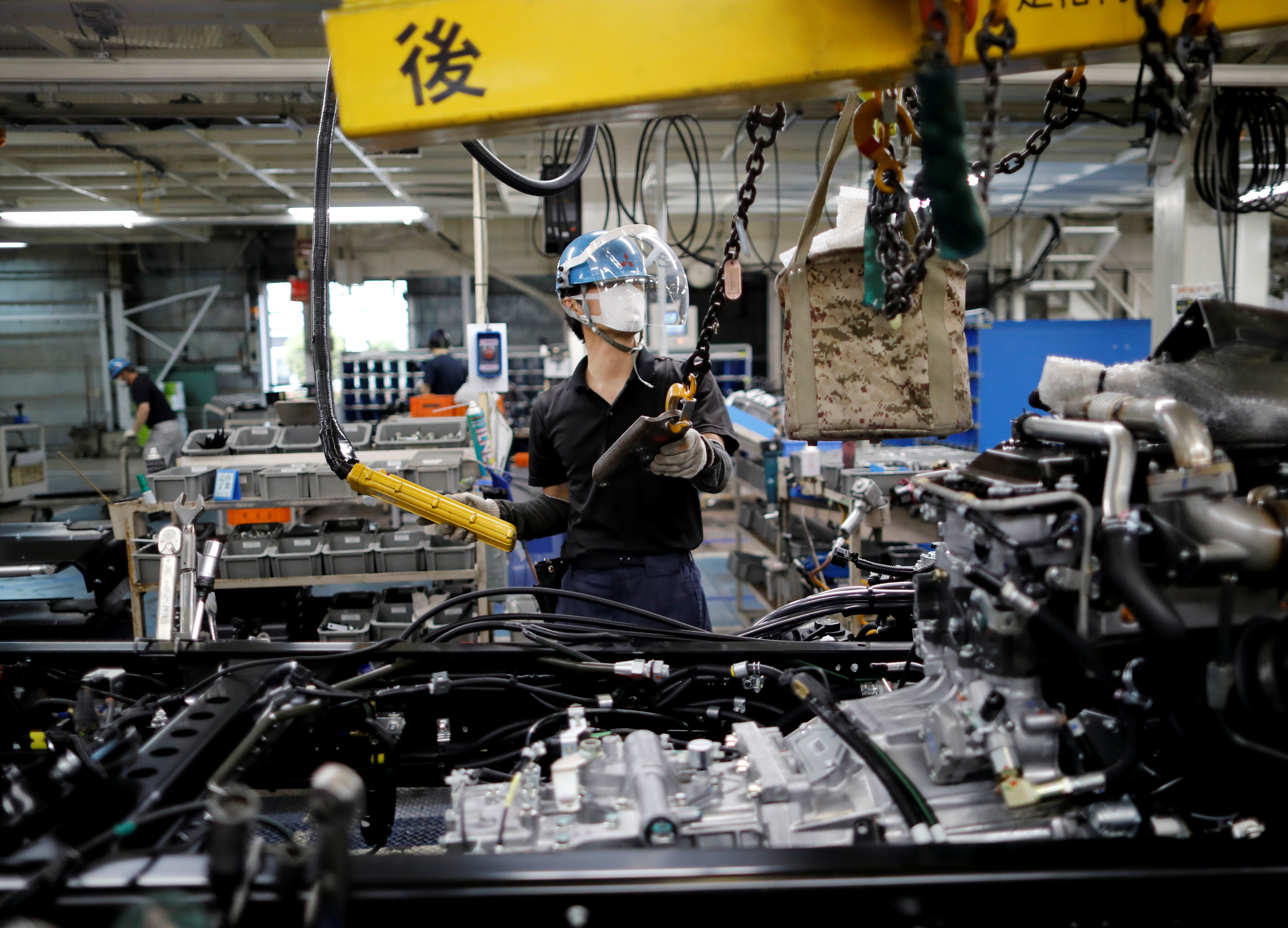 An employee wearing a protective face mask and face guard works on the automobile assembly line at Kawasaki factory of Mitsubishi Fuso Truck and Bus Corp, owned by Germany-based Daimler AG, in Kawasaki, south of Tokyo, Japan May 18, 2020.  REUTERS/Issei Kato/File Photo