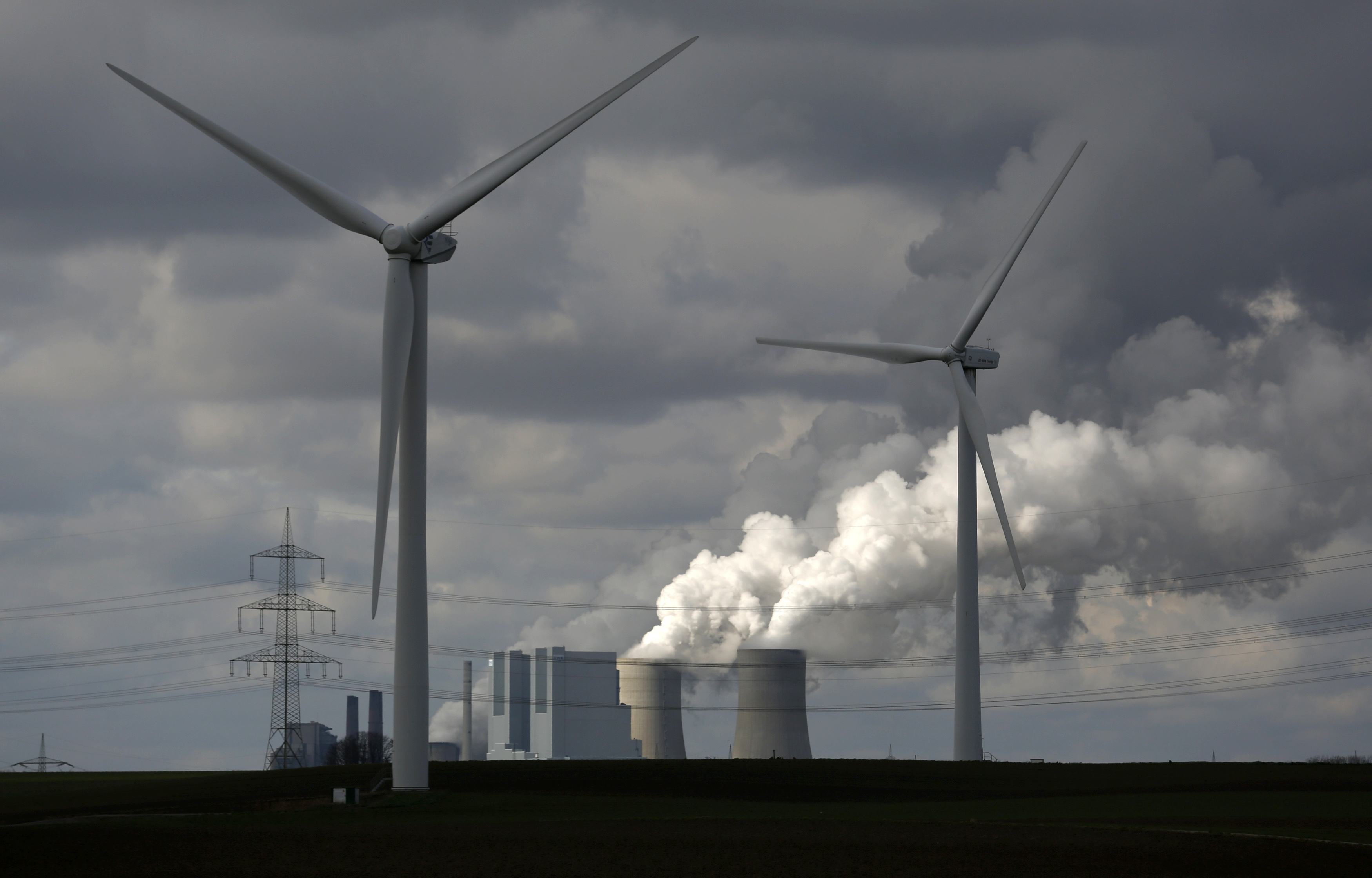 Wind turbines are seen in front of a coal power plant of German utility RWE Power near the western town of Neurath February 28, 2014. REUTERS/Ina Fassbender  (GERMANY - Tags: BUSINESS ENERGY EMPLOYMENT)