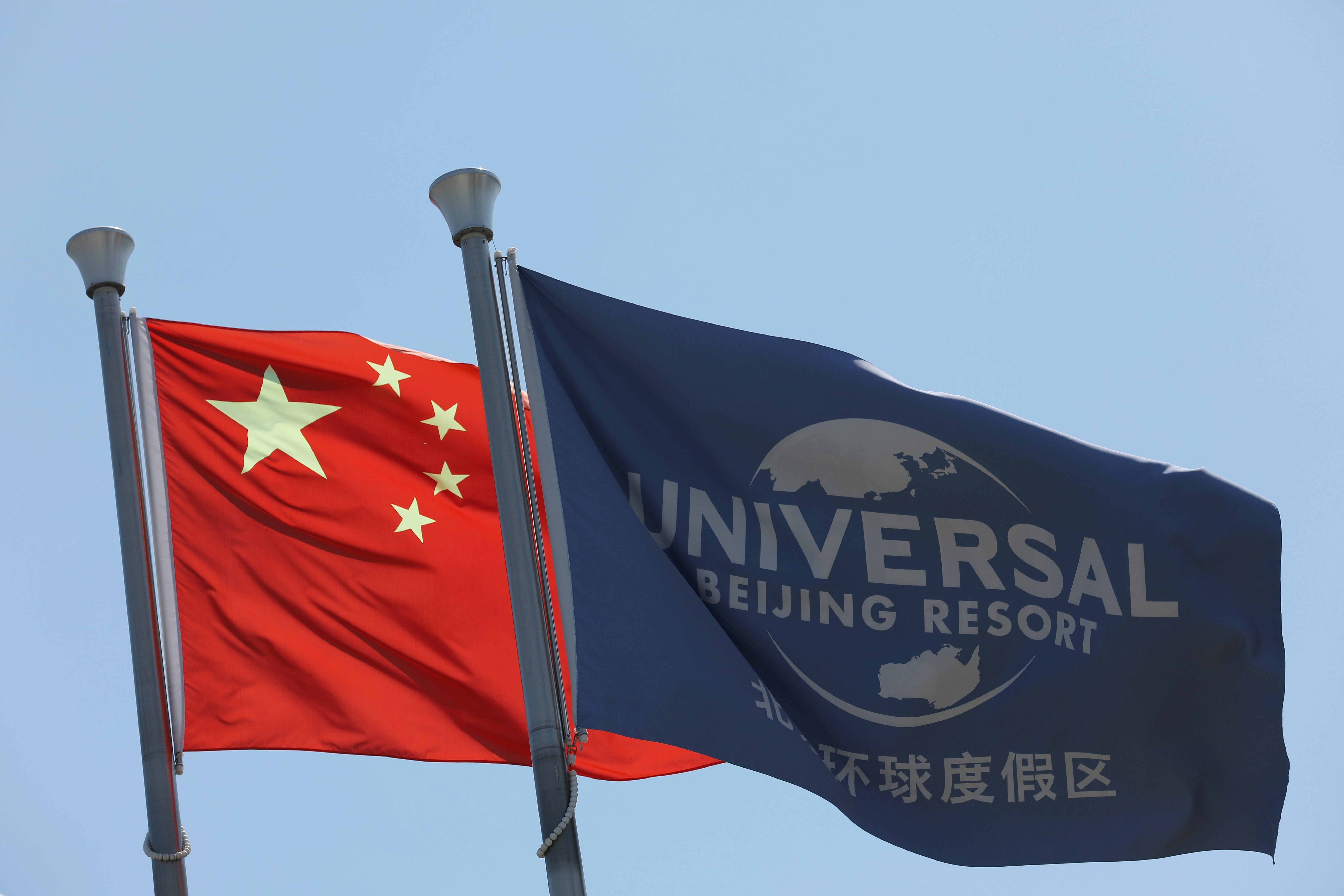 Chinese national flag flutters next to a flag of Universal Beijing Resort, ahead of the resort's opening in Beijing, China, August 27, 2021. REUTERS/Tingshu Wang/File Photo
