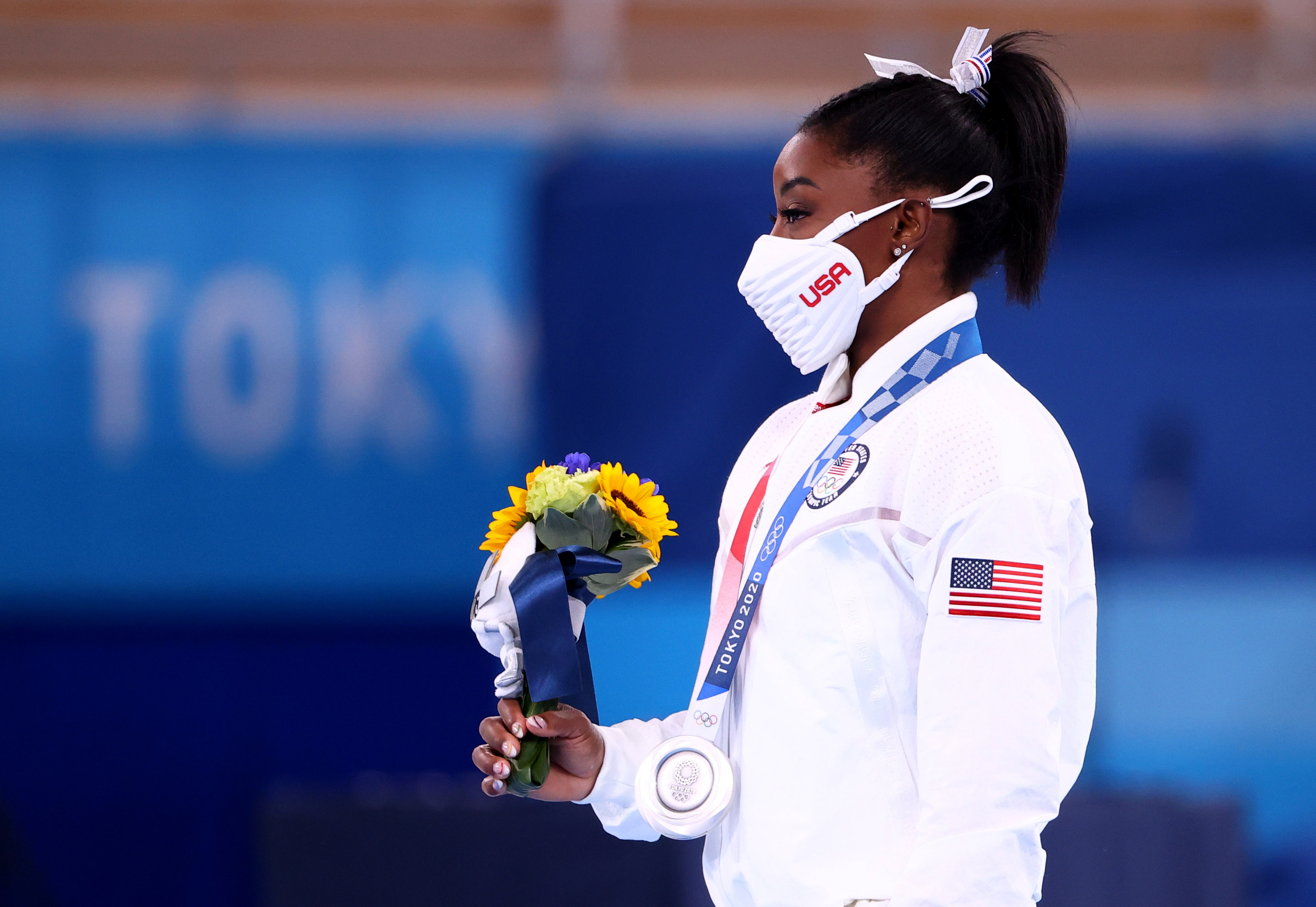 Tokyo 2020 Olympics - Gymnastics - Artistic - Women's Team - Medal Ceremony - Ariake Gymnastics Centre, Tokyo, Japan - July 27, 2021.  Silver medallist Simone Biles of the United States wearing a protective face mask holds flowers. REUTERS/Lindsey Wasson