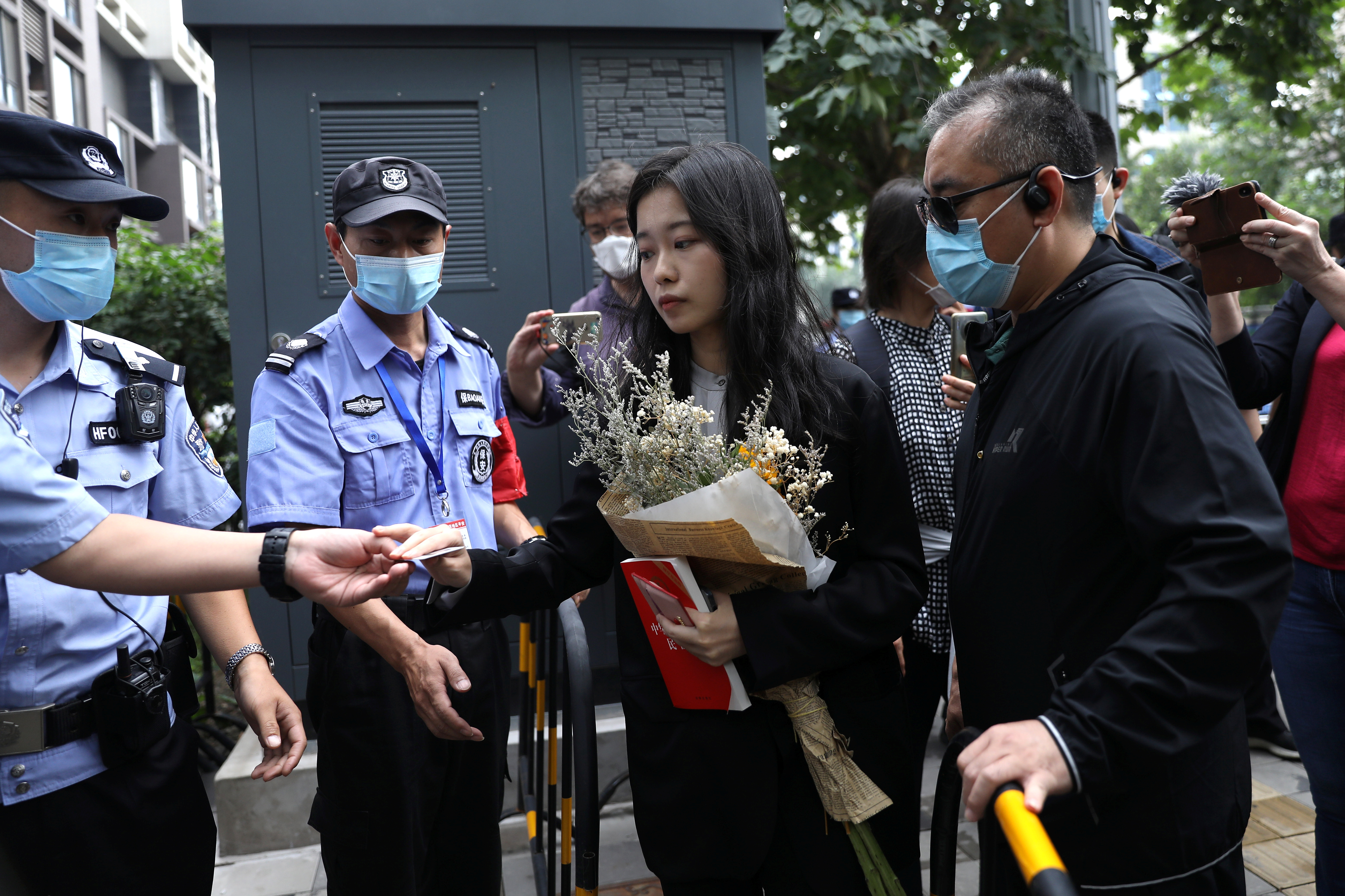 Zhou Xiaoxuan, also known by her online name Xianzi, has her identity card checked as she arrives at a court for a sexual harassment case involving a Chinese state TV host, in Beijing, China September 14, 2021. REUTERS/Tingshu Wang