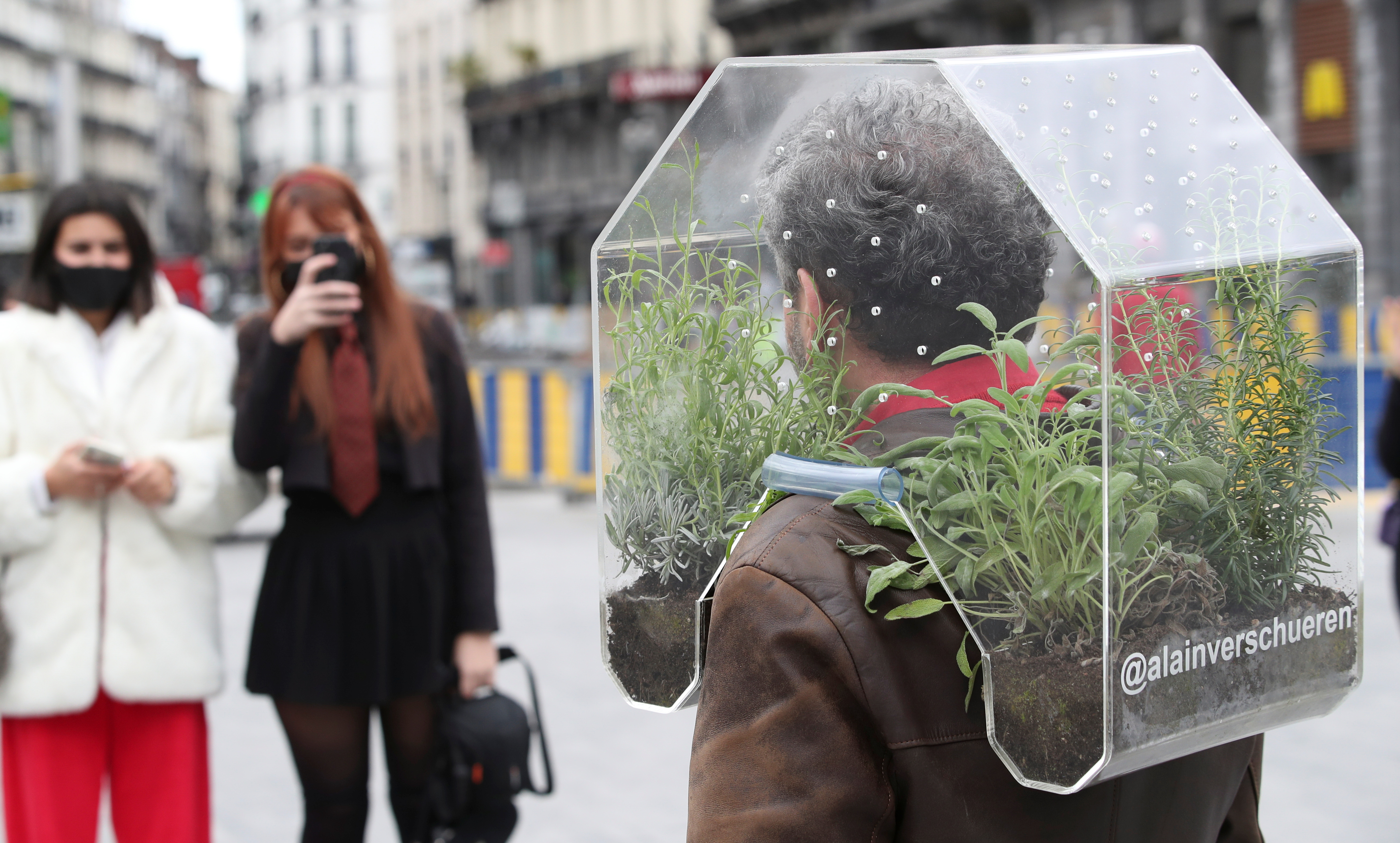 """Belgian artist Alain Verschueren wears his """"Portable Oasis"""" while performing in a street, saying he wanted to be in his bubble in the middle of the city, amid the coronavirus disease (COVID-19) outbreak in Brussels, Belgium April 16, 2021. Picture taken April 16, 2021. REUTERS/Yves Herman"""