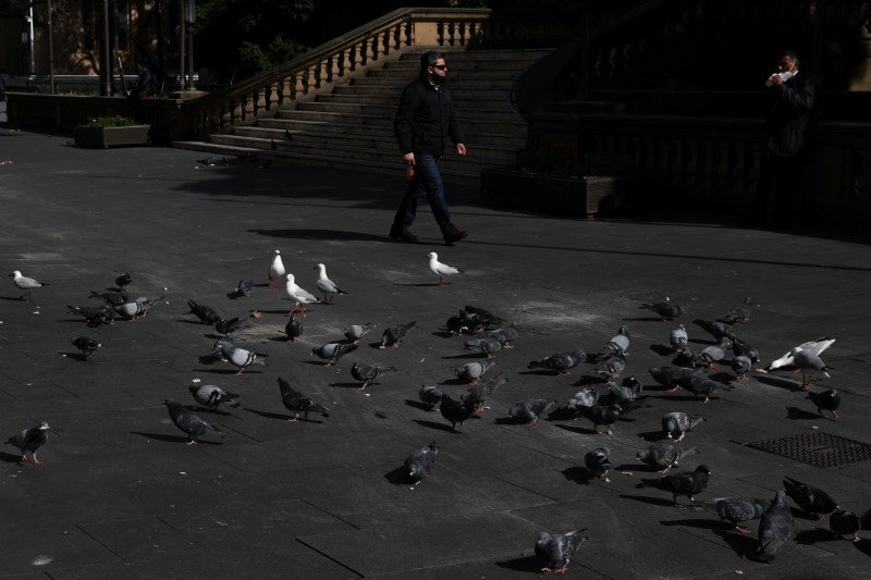 A pedestrian walks past birds congregating in a quiet city centre plaza during a lockdown to curb the spread of a coronavirus disease (COVID-19) outbreak in Sydney, Australia, August 9, 2021.  REUTERS/Loren Elliott