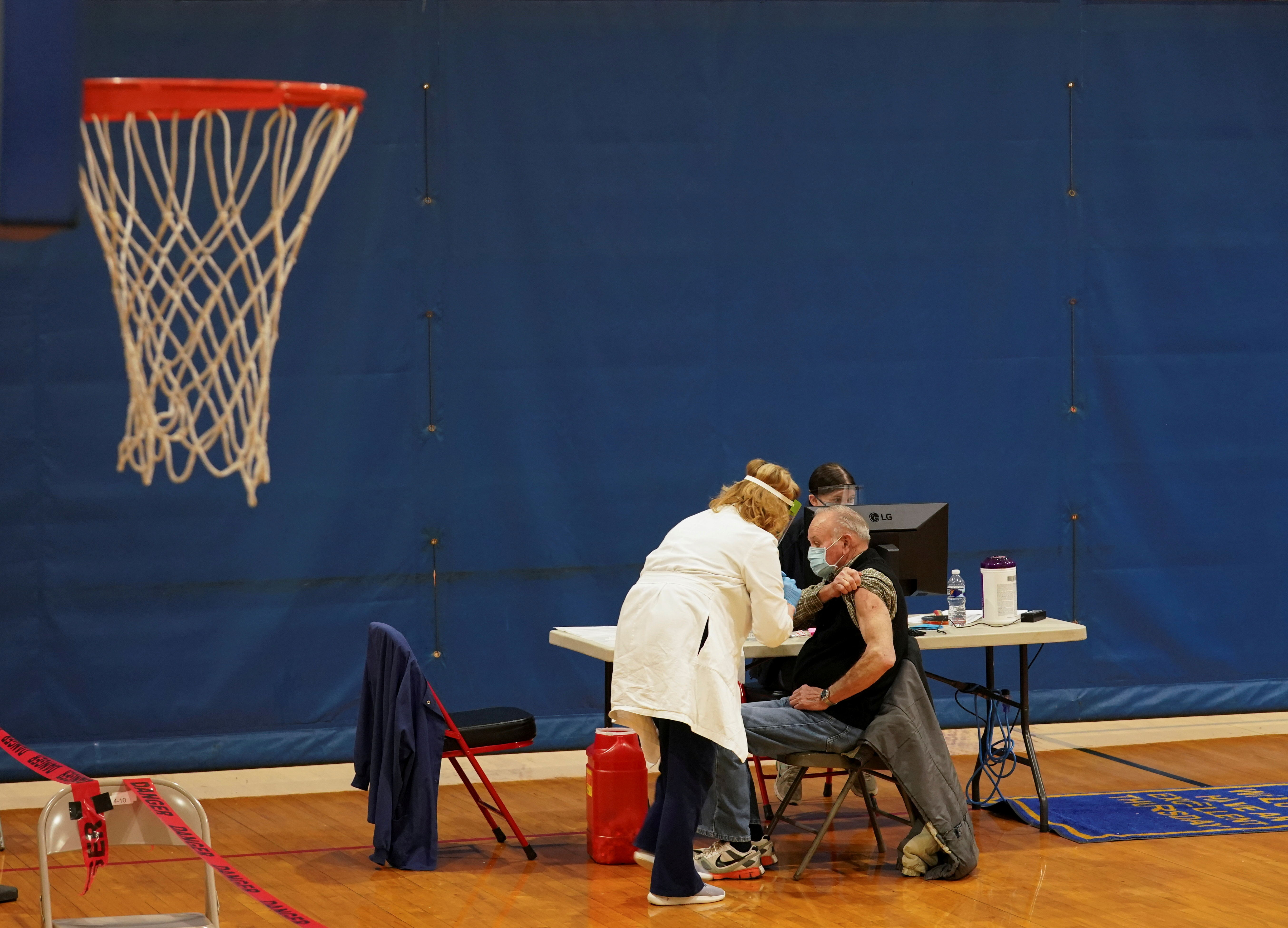 A basketball net hangs at a recreation center as patients receive their boost dose at a coronavirus disease (COVID-19) community vaccination event, as the vaccination rate in West Virginia ranks among highest in world, in Martinsburg, U.S. February 25, 2021. REUTERS/Kevin Lamarque/File Photo