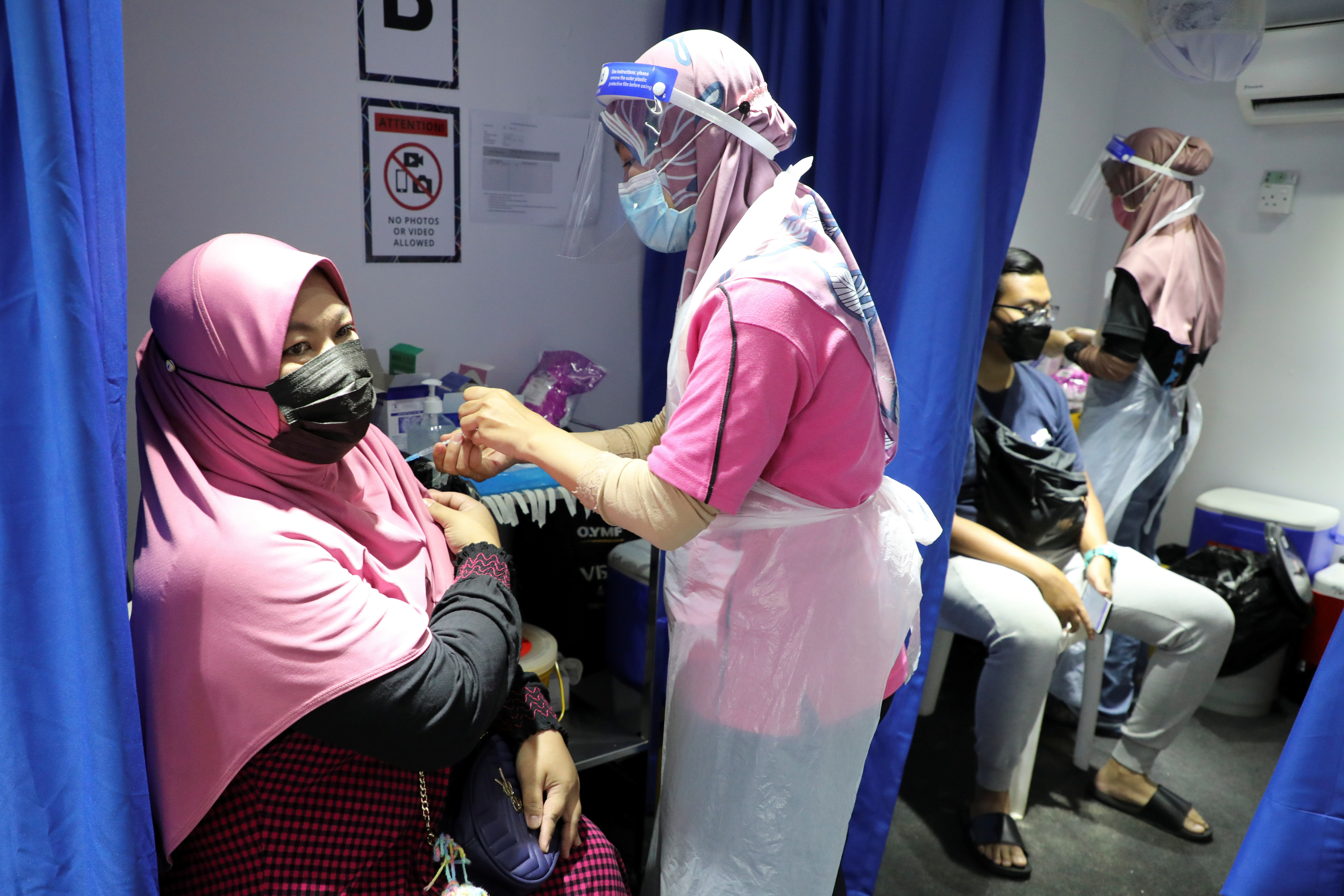 People receive doses of the Sinovac vaccine against the coronavirus disease (COVID-19) in a vaccination truck in Kuala Lumpur, Malaysia July 12, 2021. REUTERS/Lim Huey Teng