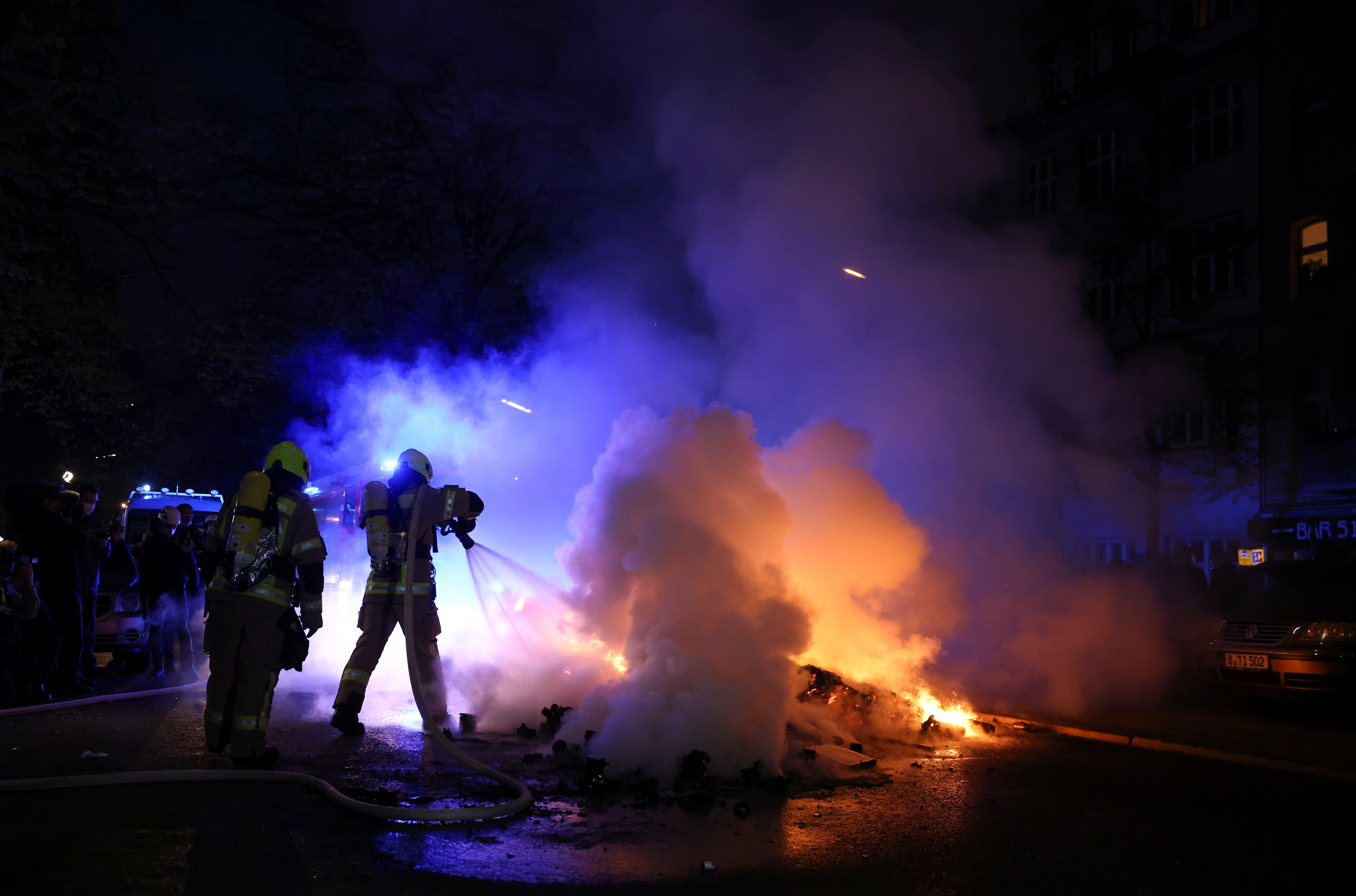 Firefighters work to extinguish a fire during a left-wing May Day demonstration, as the spread of the coronavirus disease (COVID-19) continues in Berlin, Germany, May 1, 2021. REUTERS/Christian Mang