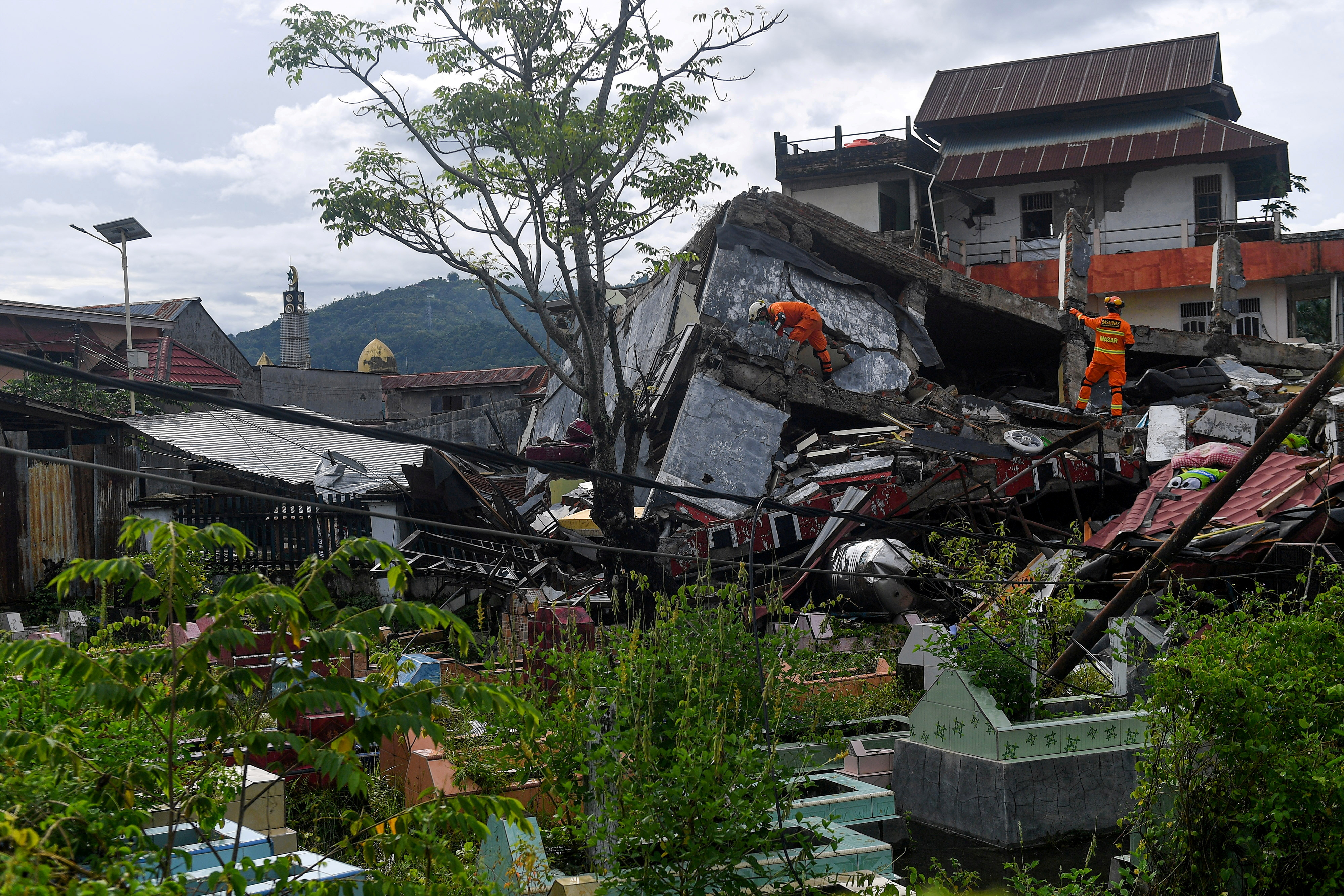 Search and rescue personnel inspect a collapsed building following an earthquake in Mamuju, West Sulawesi province, Indonesia, January 16, 2021. Sigid Kurniawan/Antara Foto via REUTERS