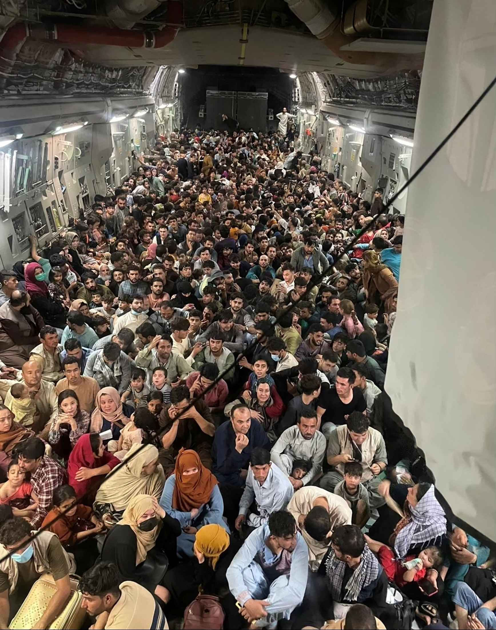 Evacuees crowd the interior of a U.S. Air Force C-17 Globemaster III transport aircraft, carrying some 640 Afghans to Qatar from Kabul, Afghanistan August 15, 2021. Picture taken August 15, 2021.  U.S. Air Force/Handout via REUTERS