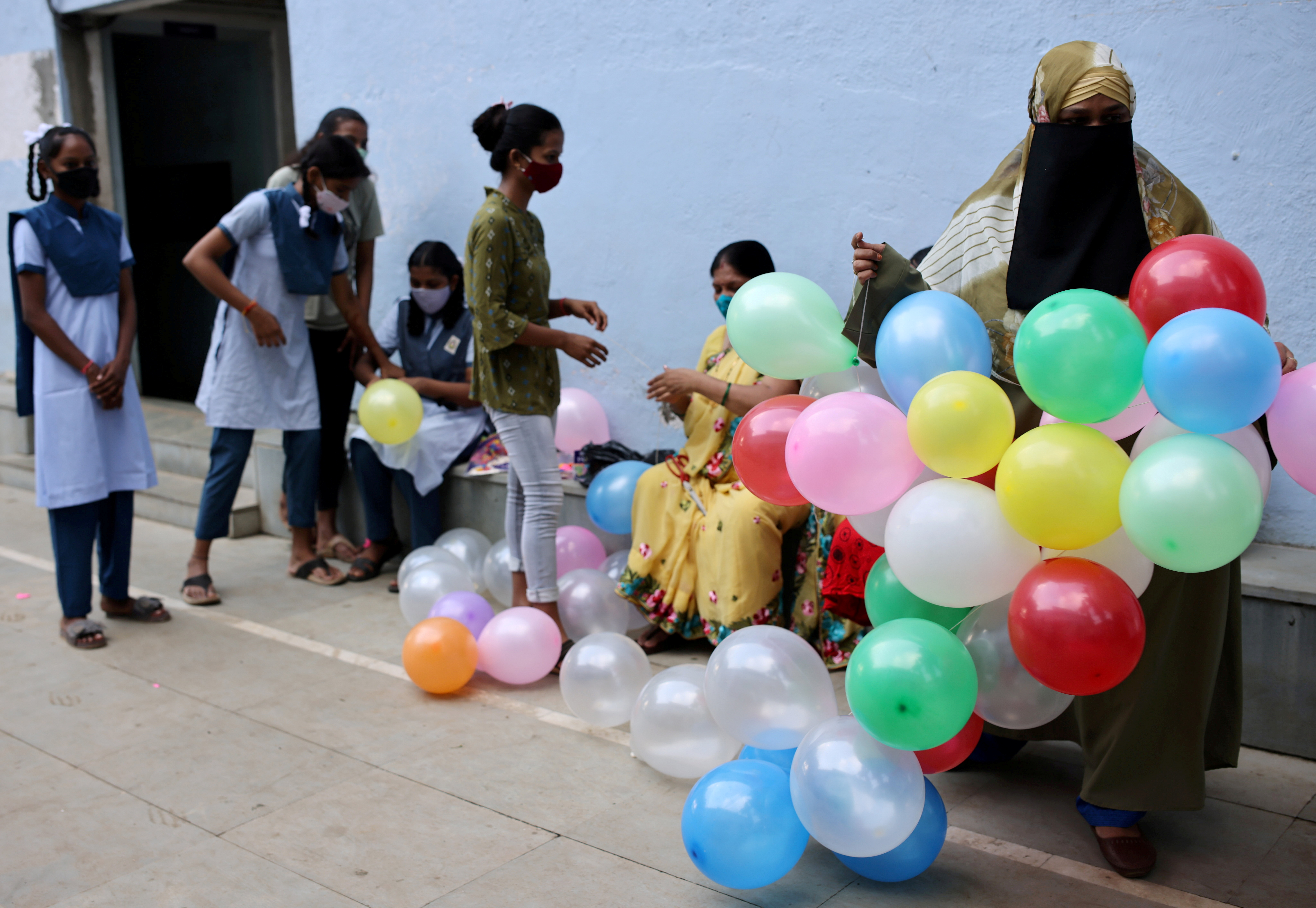 Students and teachers prepare to decorate a school following the reopening after over a year due to the coronavirus disease (COVID-19) pandemic in Mumbai, India, October 4, 2021. REUTERS/Francis Mascarenhas/File Photo