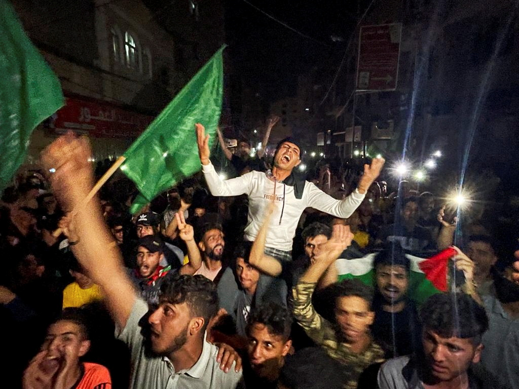 Palestinians celebrate in the streets following a ceasefire, in the southern Gaza Strip May 21, 2021. REUTERS/Ibraheem Abu Mustafa
