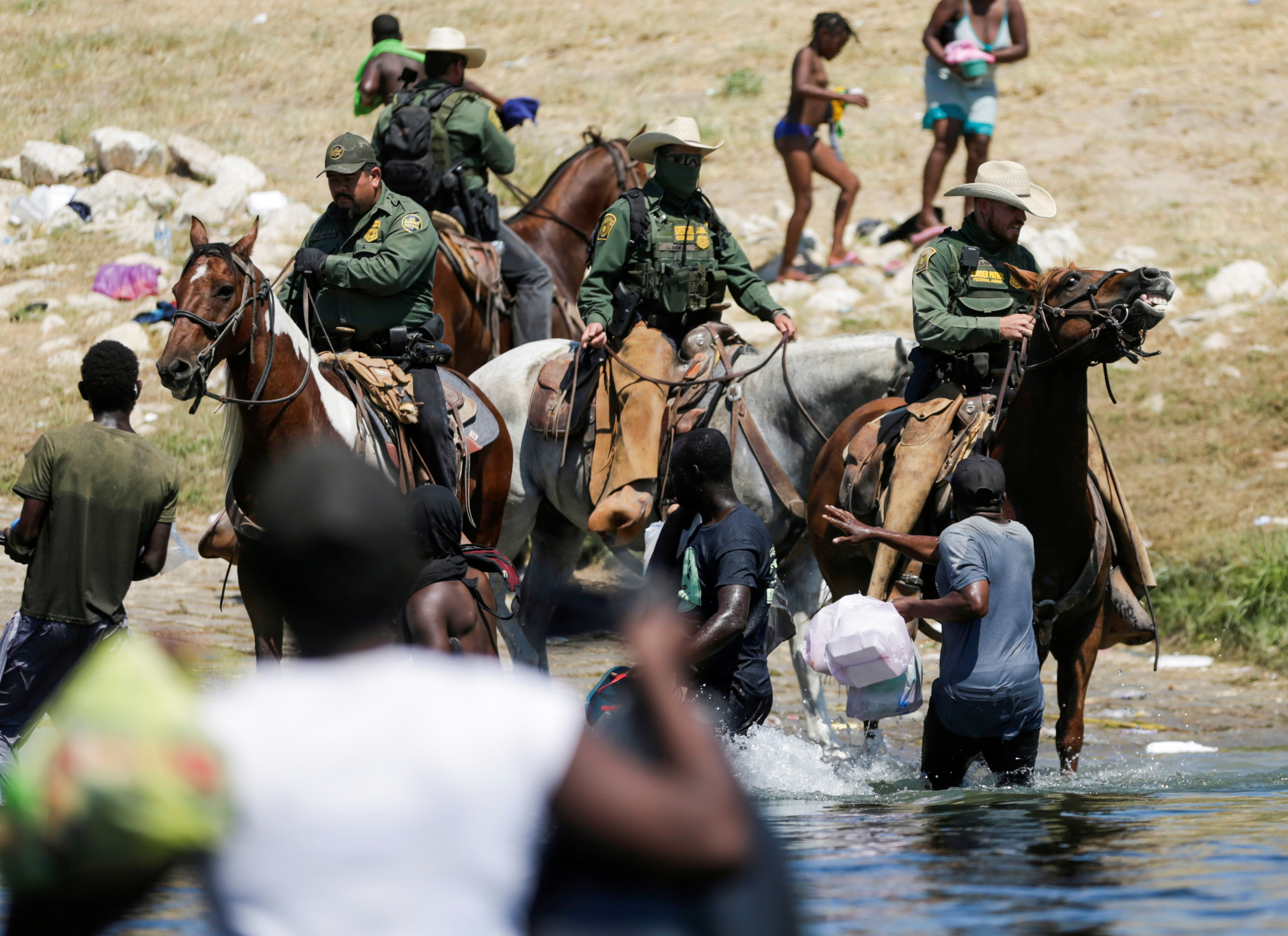 U.S. law enforcement officers on horseback block the way to migrants reaching the shores of the Rio Grande as they try to return to the United States after buying food in Mexico, as seen from Ciudad Acuna, Mexico September 19, 2021. Picture taken September 19, 2021. REUTERS/Daniel Becerril