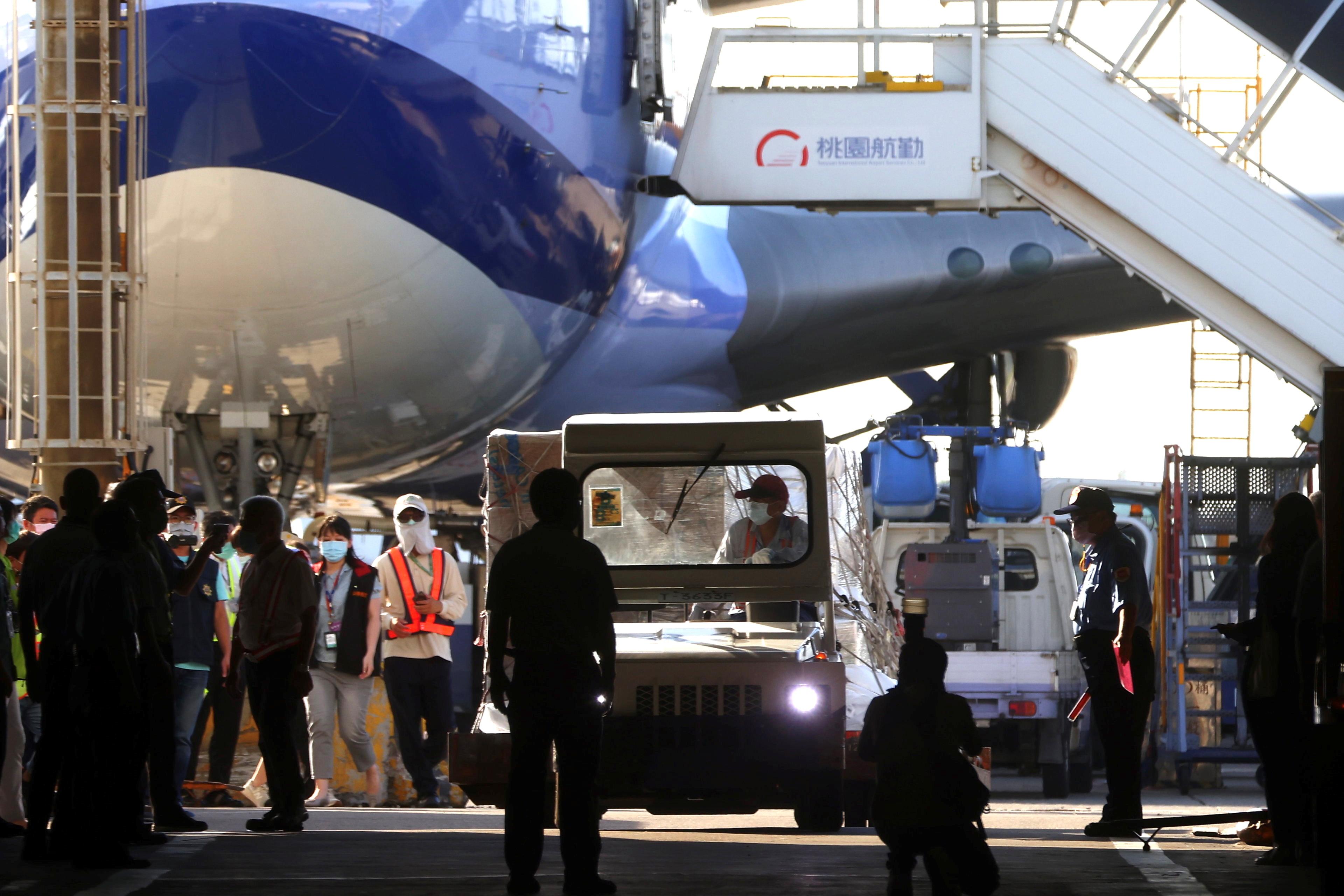 Workers transport Moderna vaccines against the coronavirus disease (COVID-19) to Taiwan Air cargo Terminal in Taoyuan, Taiwan, June 18, 2021. REUTERS/Ann Wang