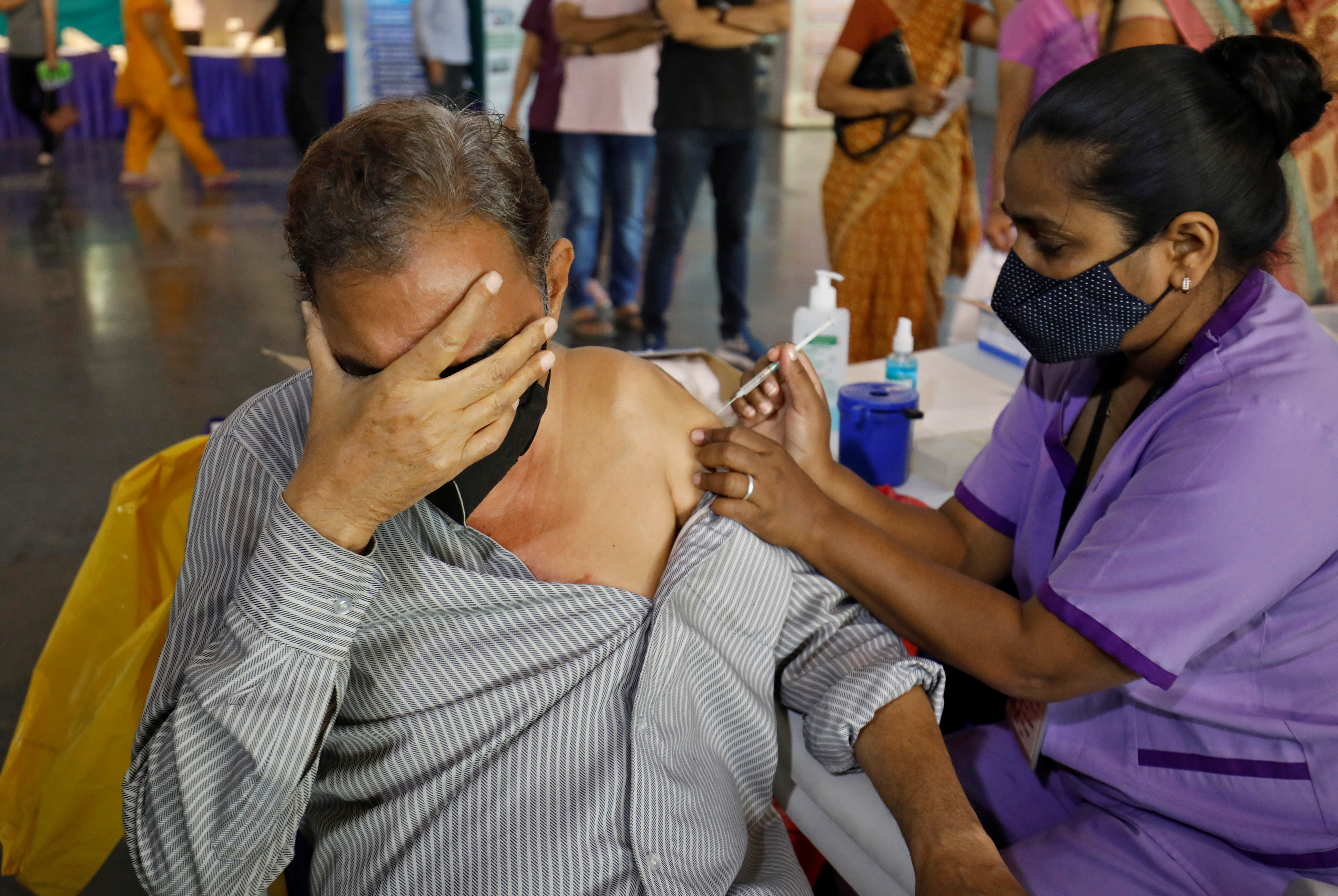 A man reacts as he receives a dose of COVISHIELD, a coronavirus disease (COVID-19) vaccine manufactured by Serum Institute of India, at an auditorium, which has been converted into a temporary vaccination centre, in Ahmedabad, India, March 26, 2021. REUTERS/Amit Dave/Files
