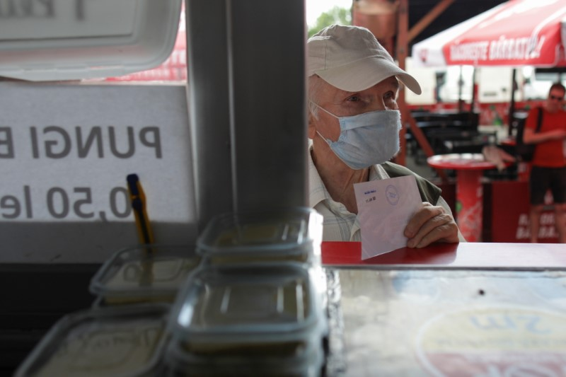Titei Constantin, 77, holds a voucher for 3 mici, traditional grilled minced meat rolls, received after being vaccinated against COVID-19, in Bucharest, Romania, June 11, 2021. Inquam Photos/Octav Ganea via REUTERS