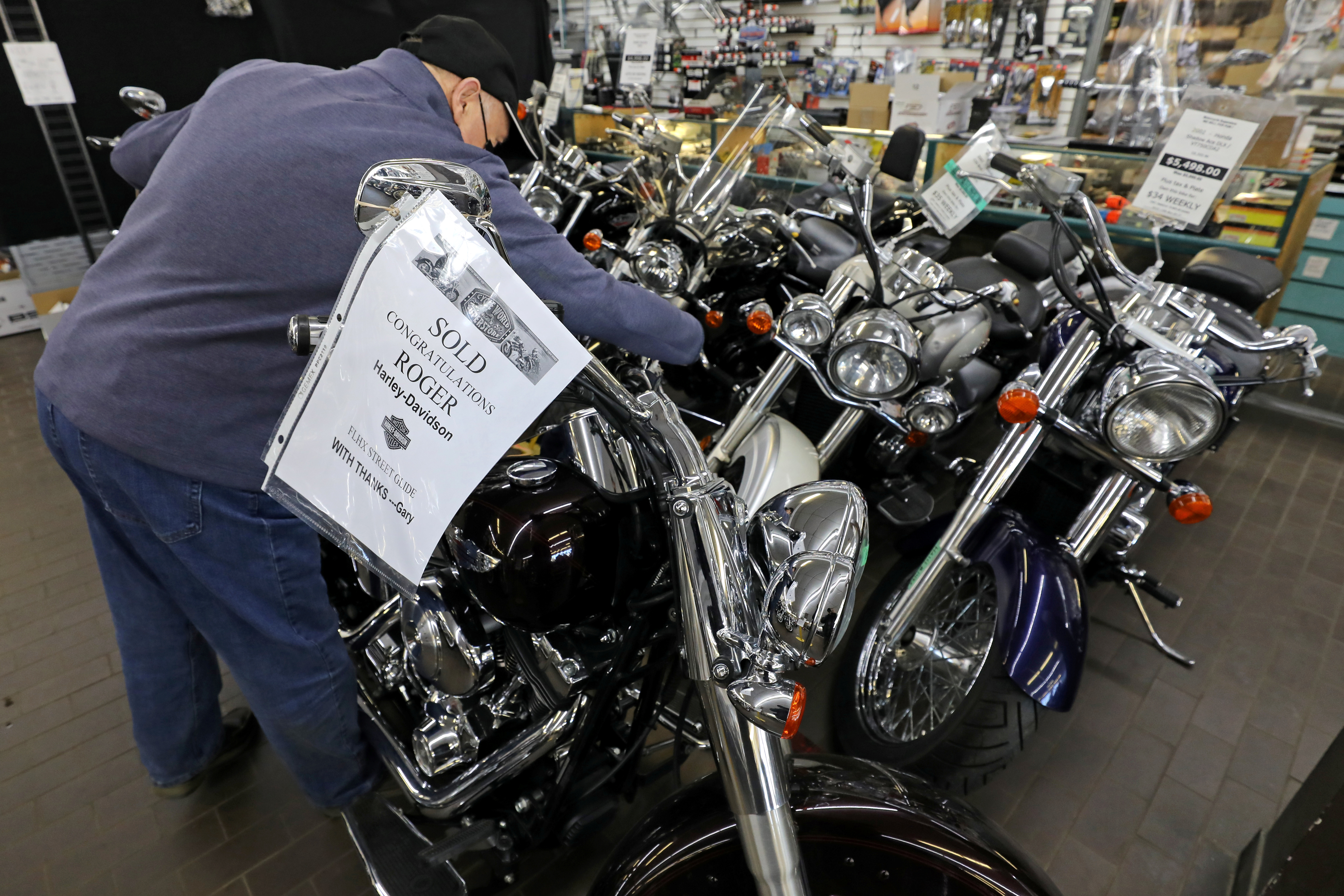 Gary Haines of Cycle World Superstore places a SOLD sign on a Harley Davidson motorcycle that had been purchased by a customer in Toronto, Ontario, Canada March 20, 2021. REUTERS/Chris Helgren