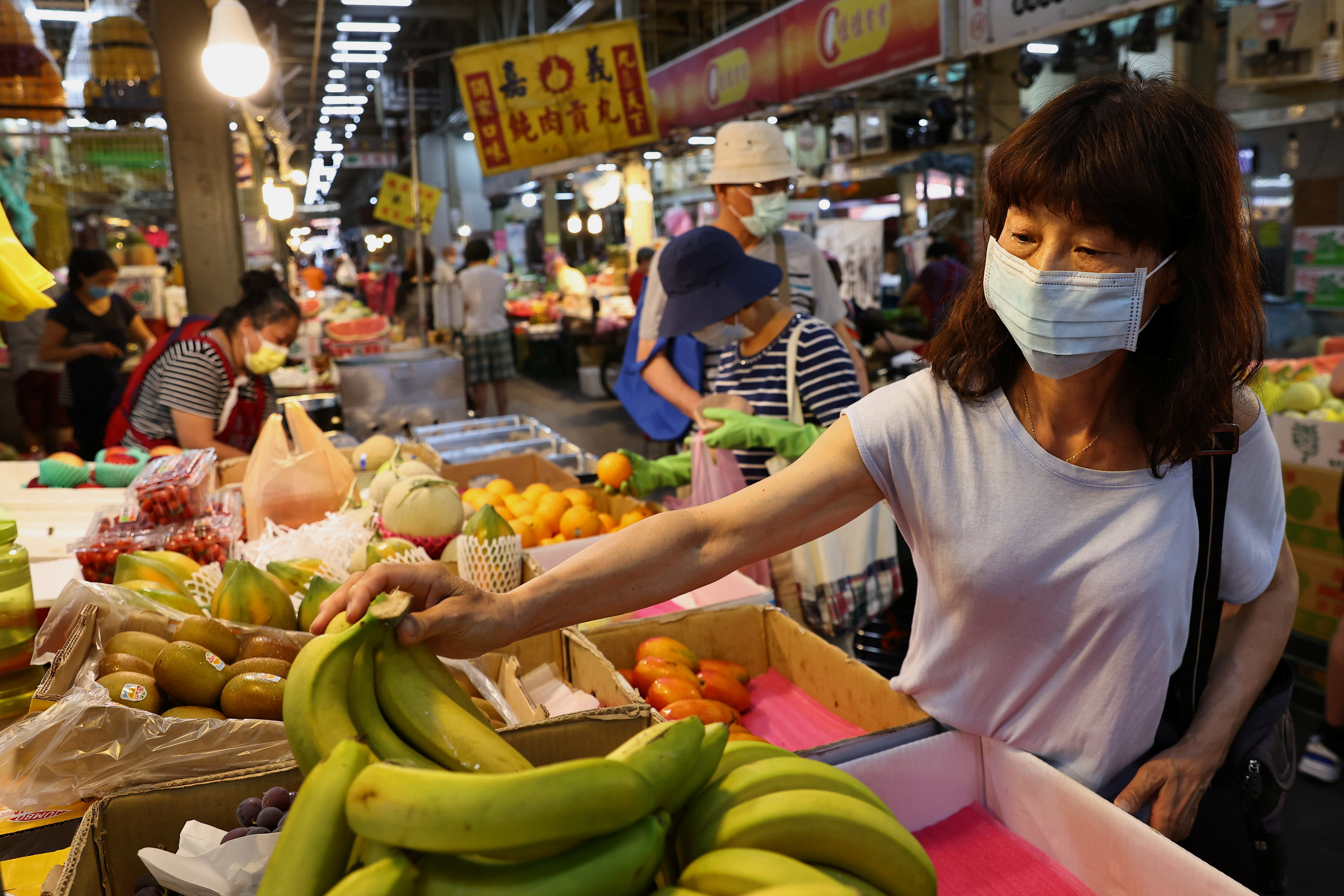 A woman wears a protective face mask while shopping for fruits at a market, amid a surge in coronavirus disease (COVID-19) infections in Taipei, Taiwan May 18, 2021. REUTERS/Ann Wang
