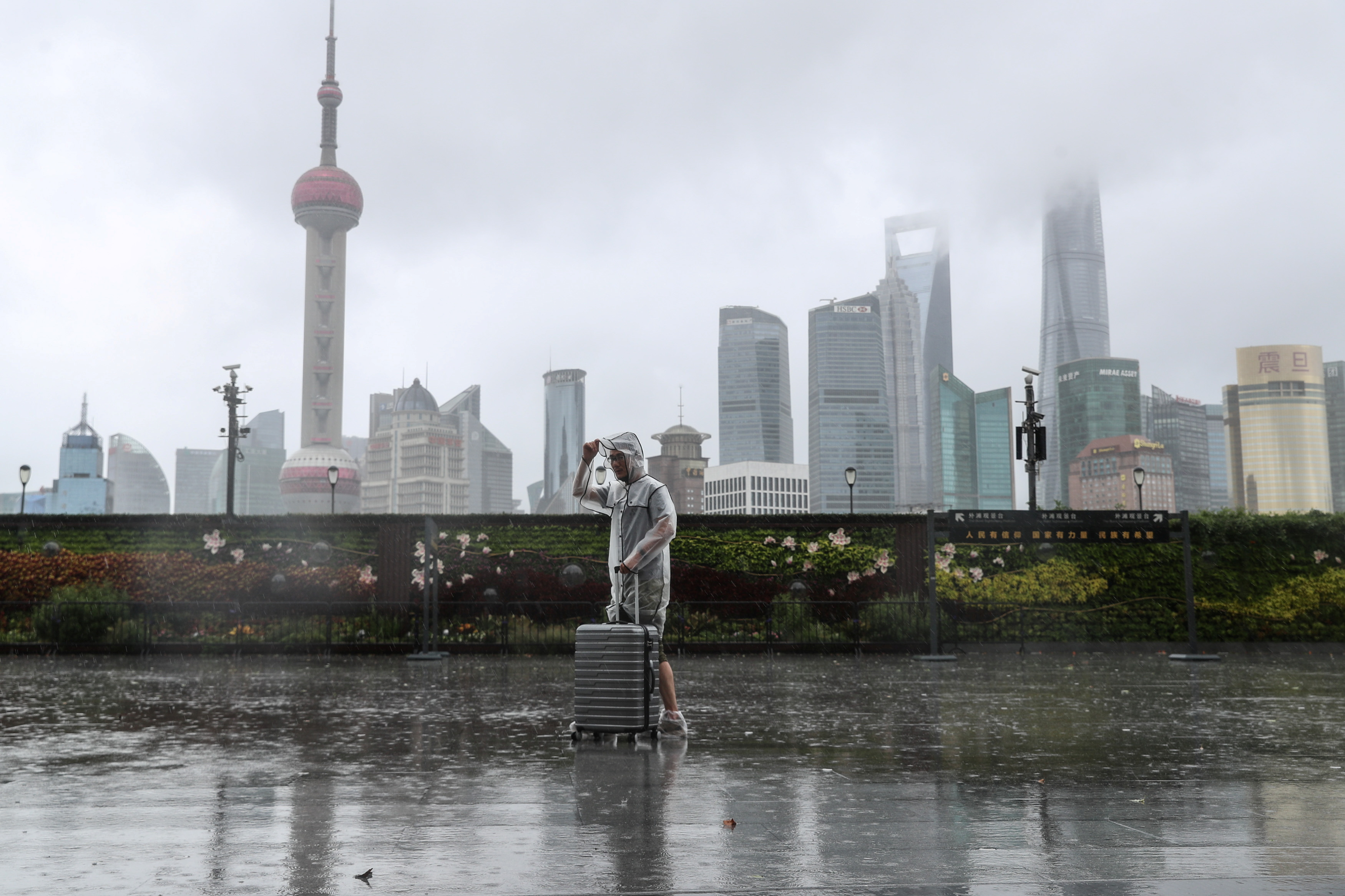 A man with luggage walks in the rain on The Bund as Typhoon In-fa approaches Shanghai, China July 25, 2021. cnsphoto via REUTERS