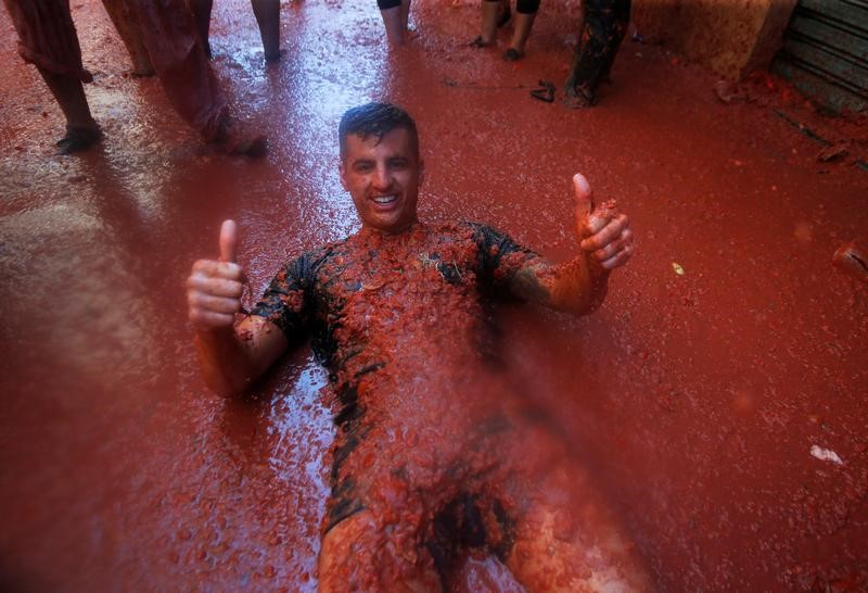 A reveller gives a thumbs up as he lies in tomato pulp during the annual
