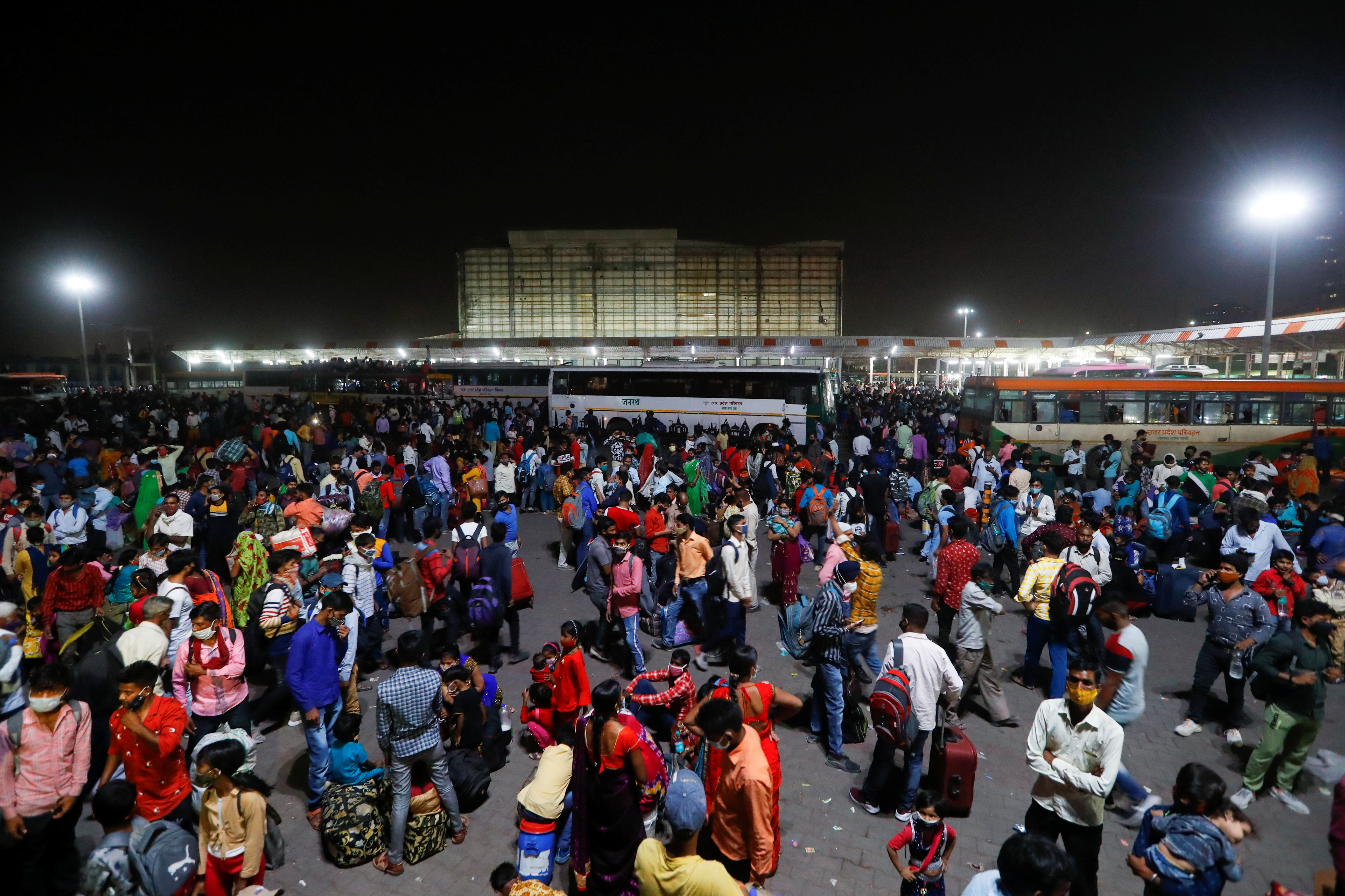 Migrant workers gather at a bus station to board buses to return to their villages after Delhi government ordered a six-day lockdown to limit the spread of the coronavirus disease (COVID-19), in Ghaziabad on the outskirts of New Delhi, India, April 19, 2021. REUTERS/Adnan Abidi