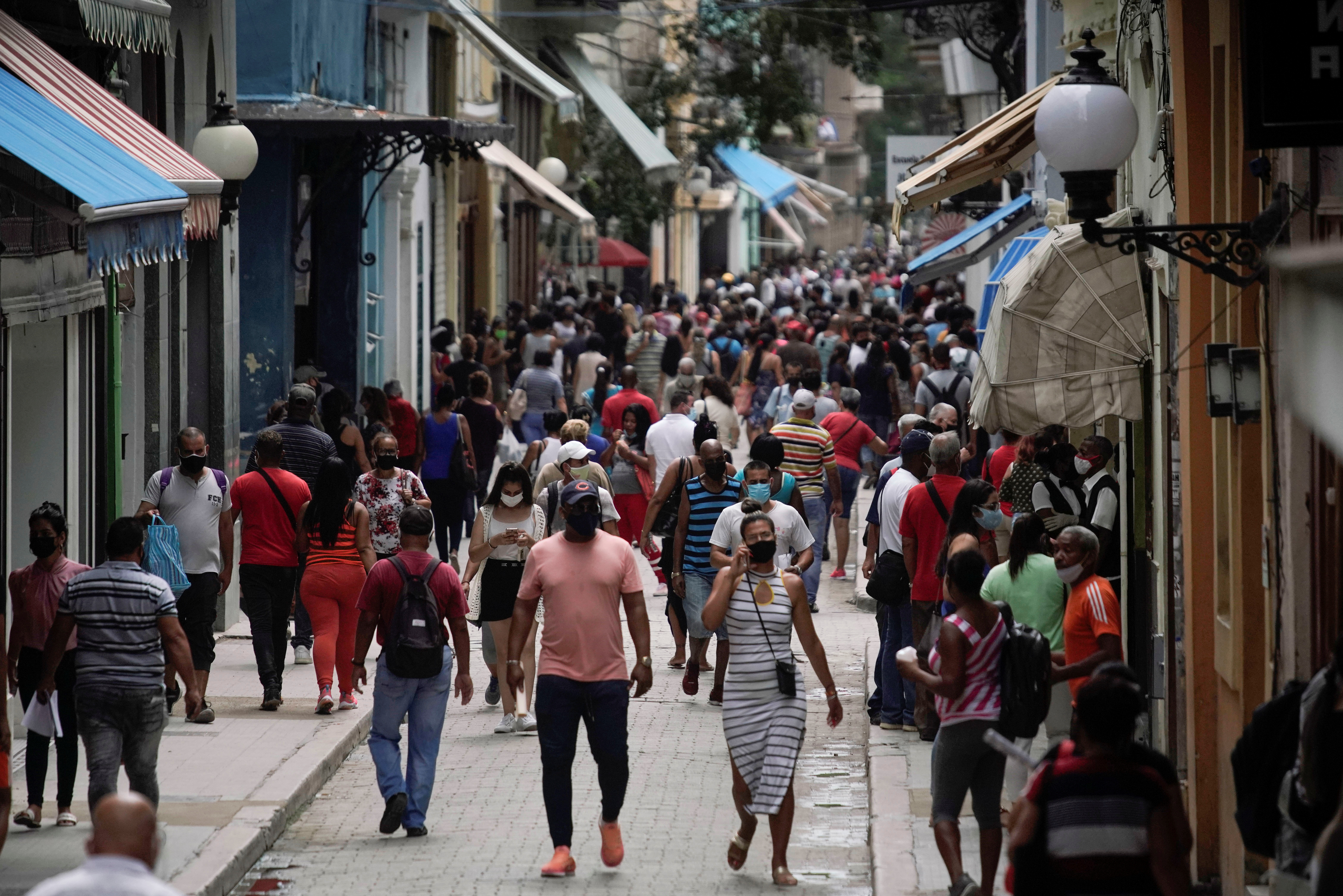 People walk in a commercial street amid the rise in cases of the coronavirus disease (COVID-19), in Havana, Cuba, June 15, 2021.  REUTERS/Alexandre Meneghini