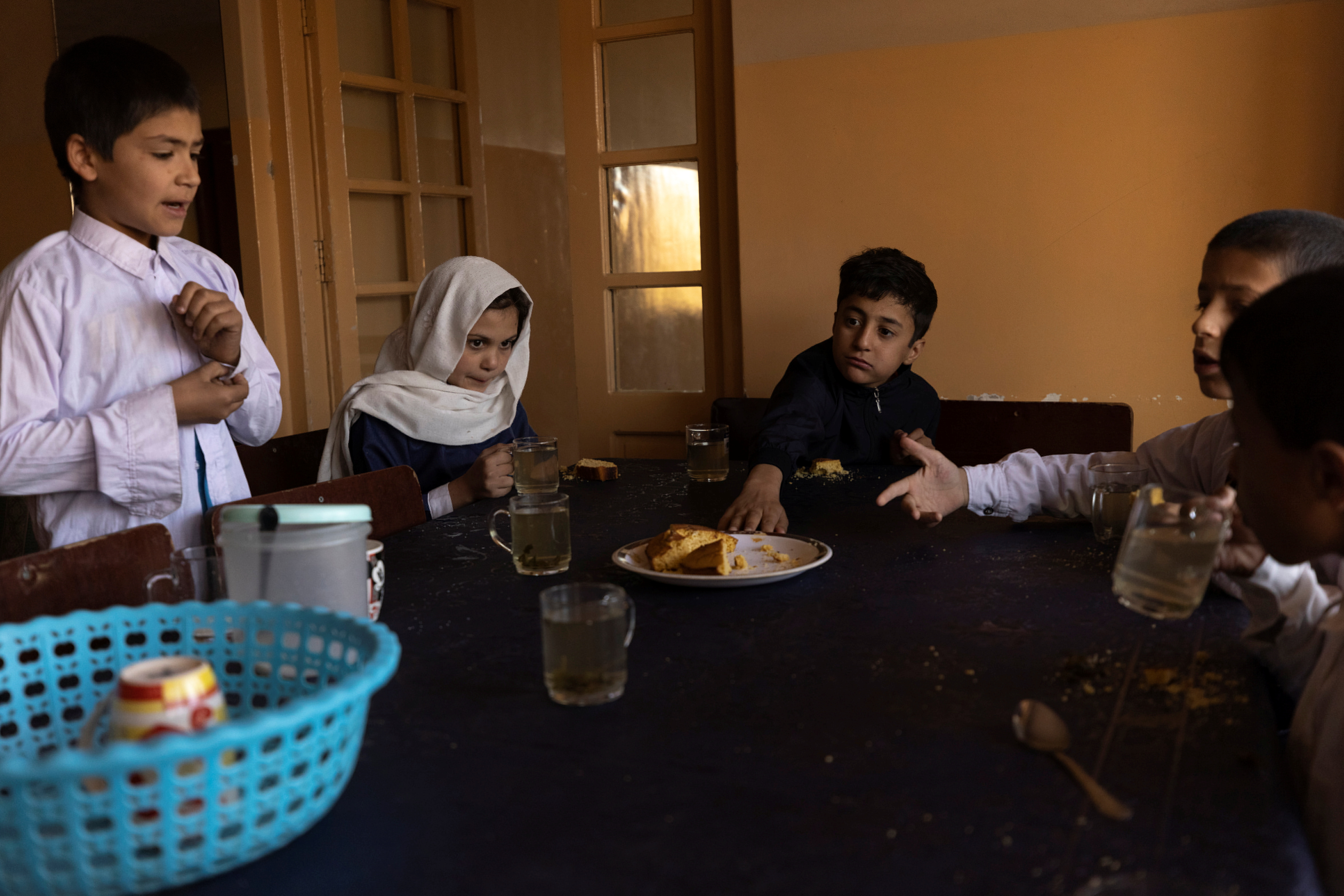 Samira, 9, and other children share tea and bread for breakfast at the orphanage before going to school in Kabul, Afghanistan, October 12, 2021. Samira wants to be a doctor when she grows up.