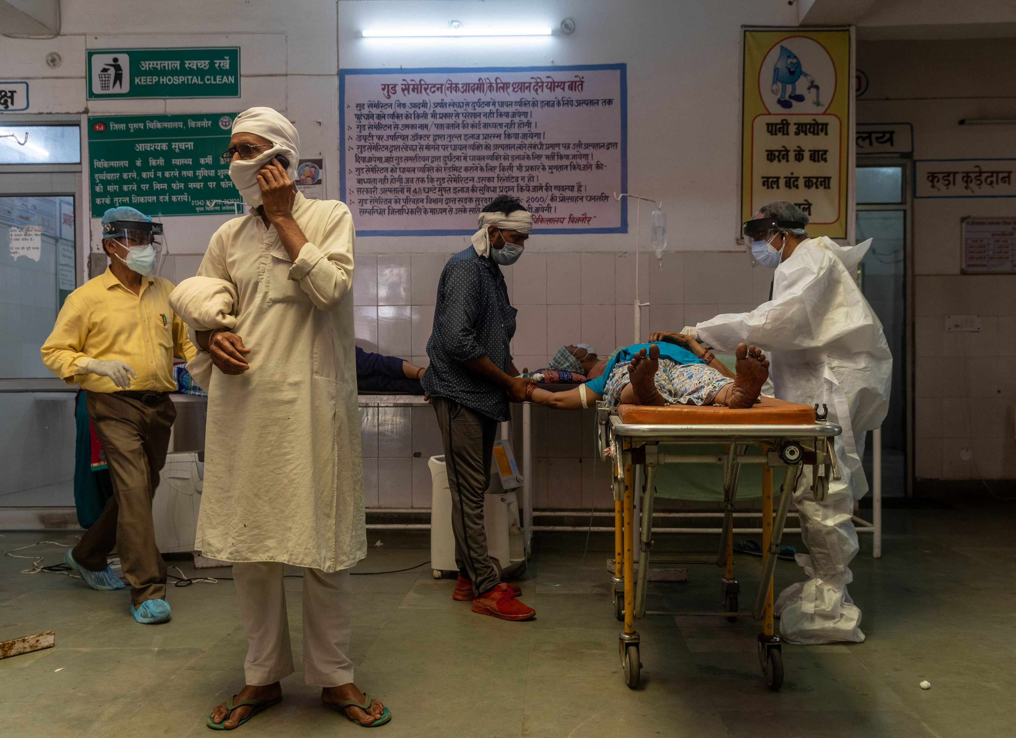 A man speaks on the phone as a doctor tries to revive his wife inside an emergency ward of a government-run hospital, amidst the coronavirus disease (COVID-19) pandemic, in Bijnor district, Uttar Pradesh, India, May 11, 2021. REUTERS/Danish Siddiqui