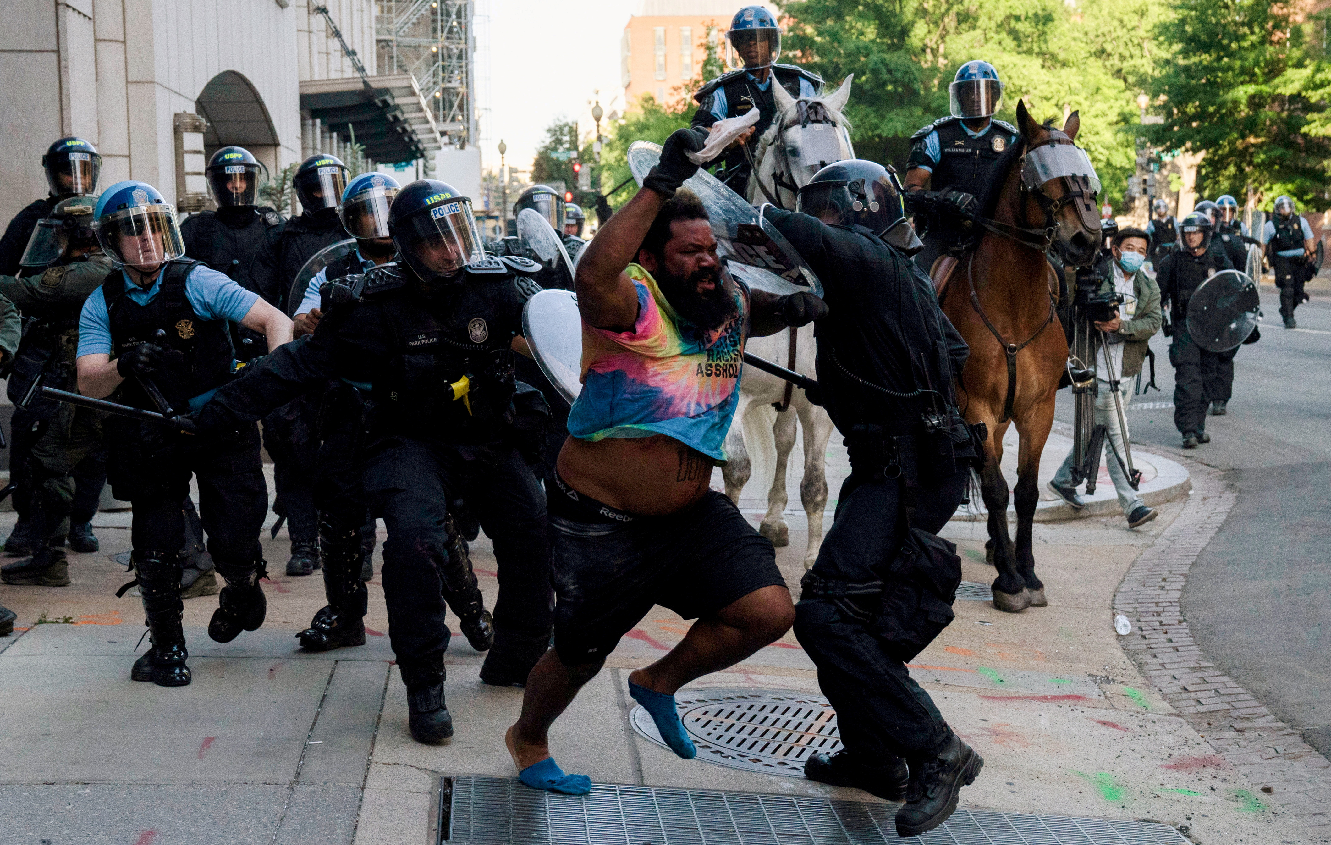 Riot police chase a man as they rush protestors to clear Lafayette Park and the area around it across from the White House for President Donald Trump to be able to walk through for a photo opportunity in front of St. John's Episcopal Church, during a rally against the death in Minneapolis police custody of George Floyd, near the White House, in Washington, U.S. June 1, 2020. REUTERS/Ken Cedeno