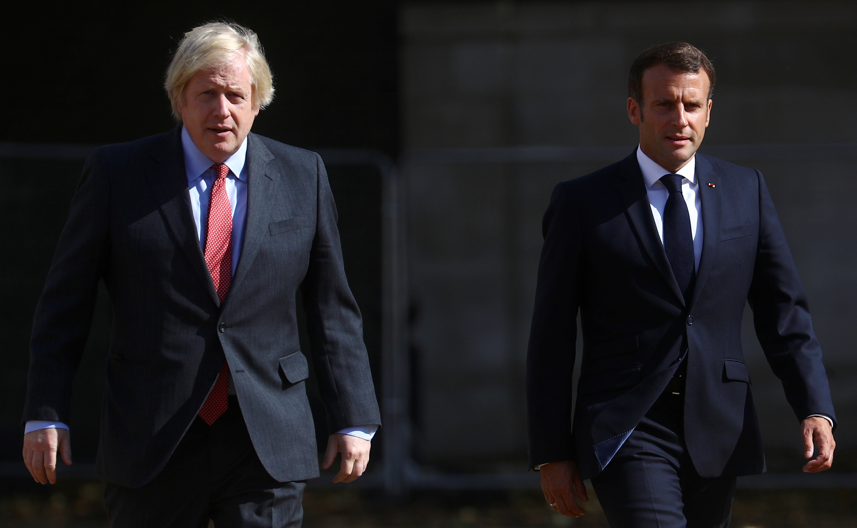 British Prime Minister Boris Johnson and French President Emmanuel Macron walk after watching The Red Arrows and La Patrouille de France perform a flypast, at Horse Guards Parade in London, Britain, June 18, 2020. REUTERS/Hannah McKay/Pool