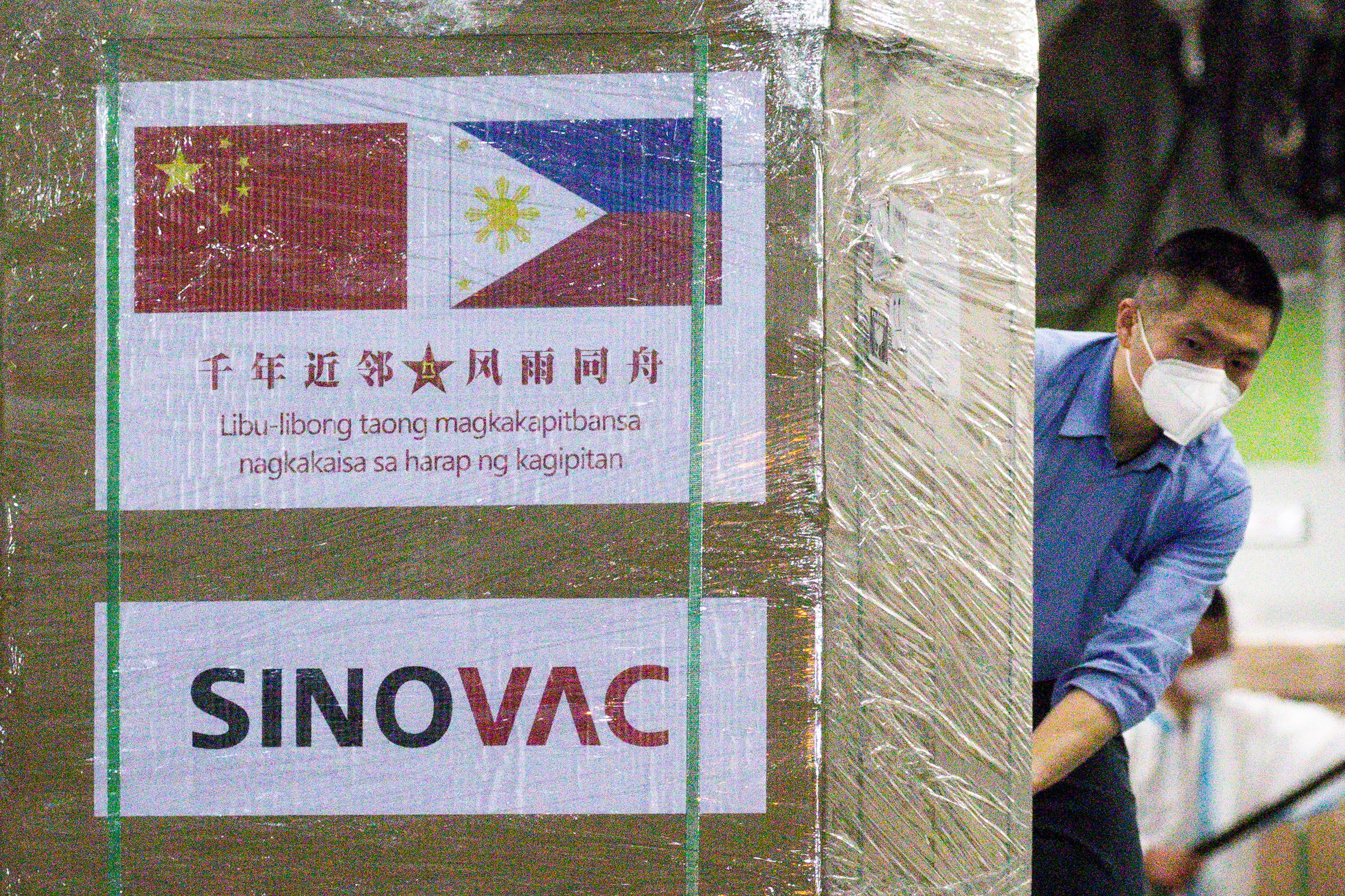 A worker unloads a box of Sinovac Biotech's CoronaVac vaccines against the coronavirus disease (COVID-19) from a Chinese military aircraft at Villamor Air Base in Pasay, Metro Manila, Philippines, February 28, 2021. REUTERS/Eloisa Lopez