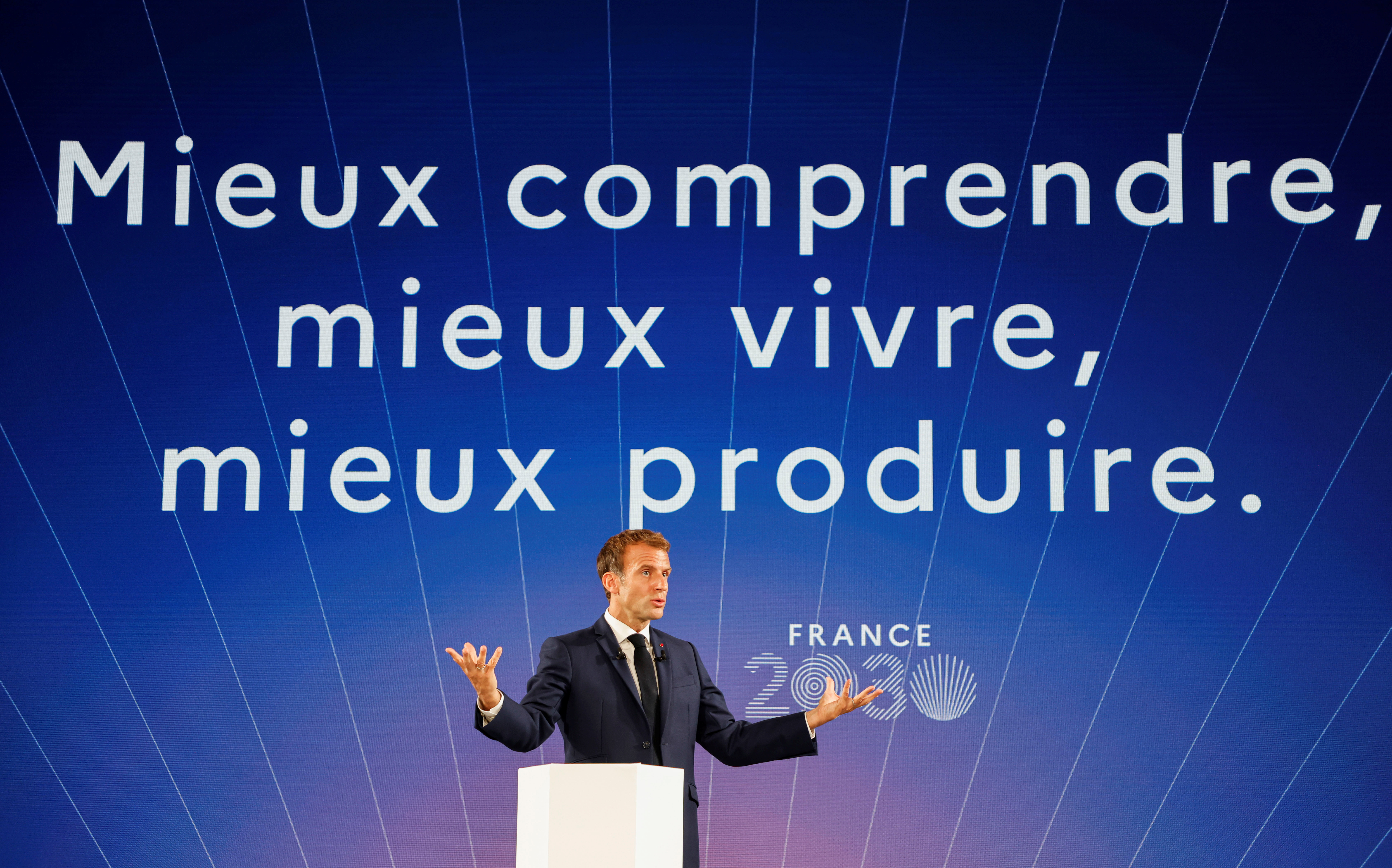 French President Emmanuel Macron speaks in front of a screen with a sentence reading