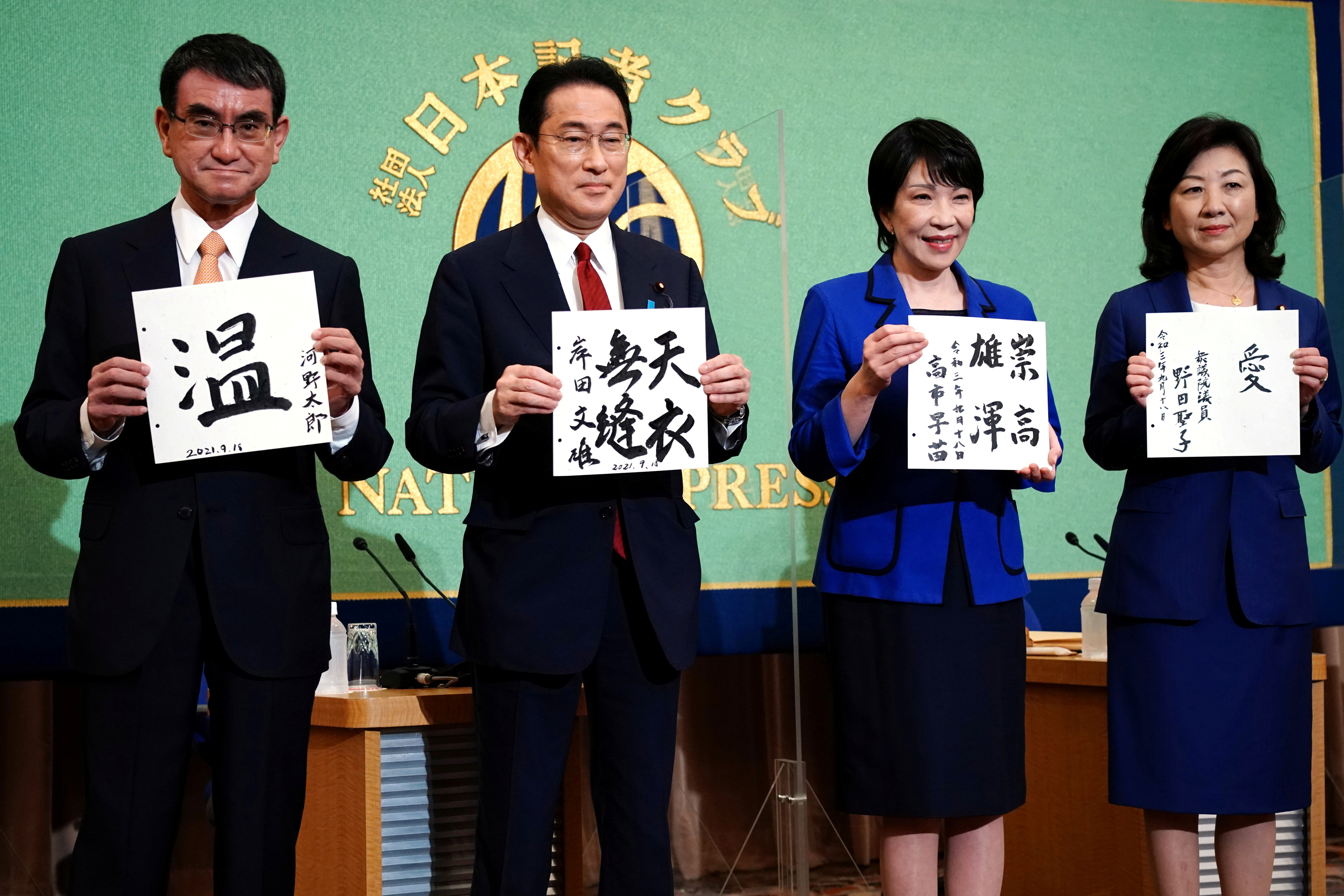 Candidates for the presidential election of the ruling Liberal Democratic Party pose with papers with their sign and words prior to a debate session held by Japan National Press Club September 18, 2021 in Tokyo, Japan. The contenders are (L to R) Taro Kono, the cabinet minister in charge of vaccinations, Fumio Kishida, former foreign minister, Sanae Takaichi, former internal affairs minister, and Seiko Noda, former internal affairs minister. Eugene Hoshiko/Pool via REUTERS